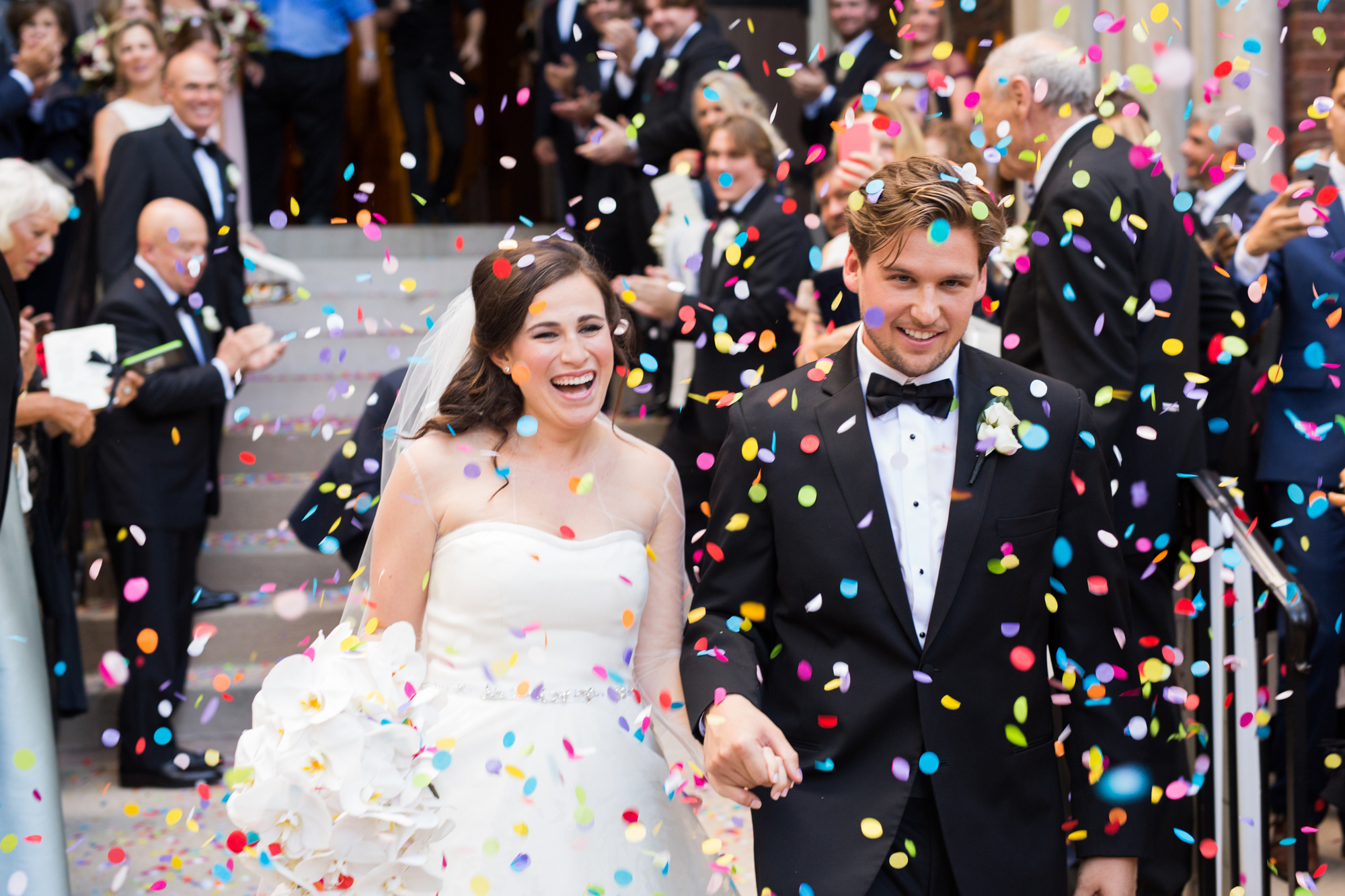 Guests throw confetti as bride and groom exit their wedding ceremony in Chicago, Illinois.