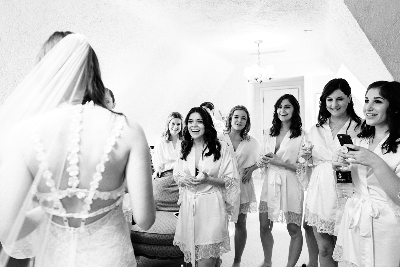 Bridesmaids see bride in her gown for the first time on her wedding day at Riverbend in Kohler, WI