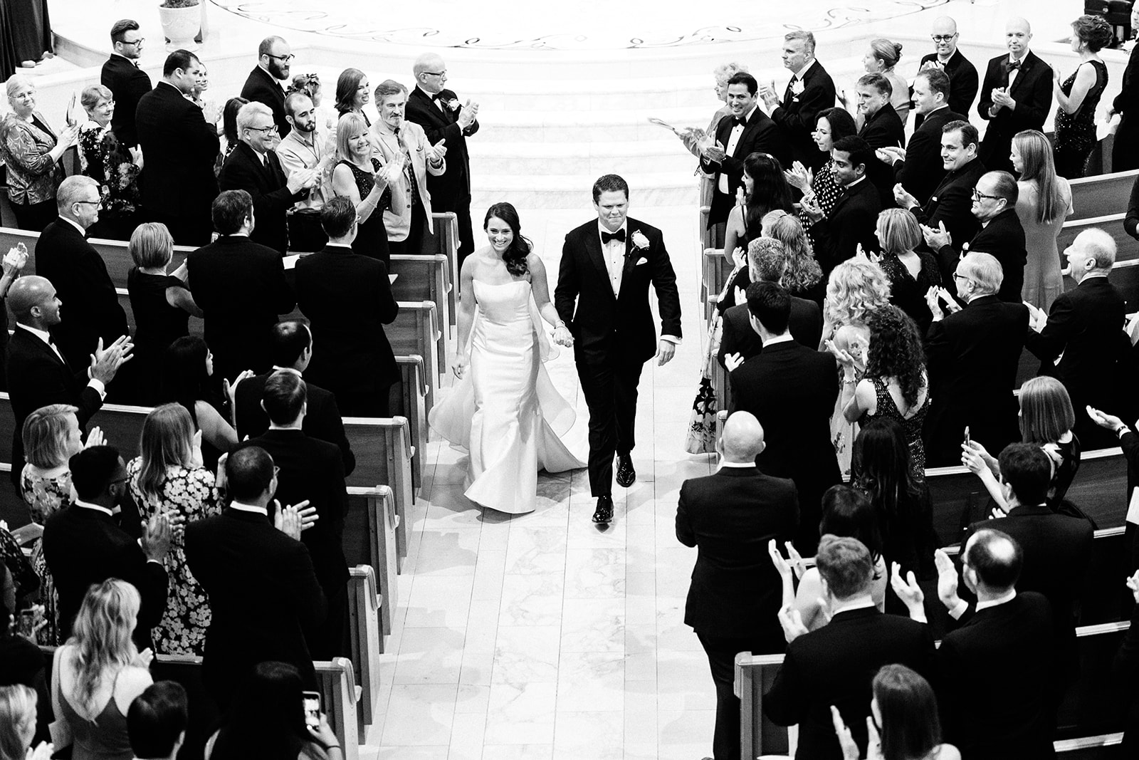 Shooting the recessional from the balcony allows us to frame the bride and groom with all of their guests during one of the most exciting parts of the day!