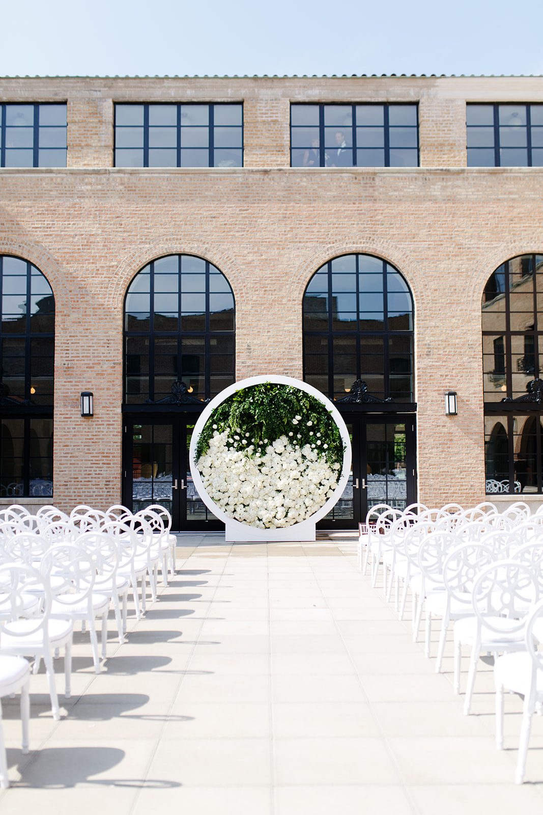 Jesse Deckard of Bliss Weddings and Events worked his magic on the modern design. White chairs lined the aisle leading up to this amazing circular ceremony backdrop of greenery, roses, and hydrangeas.