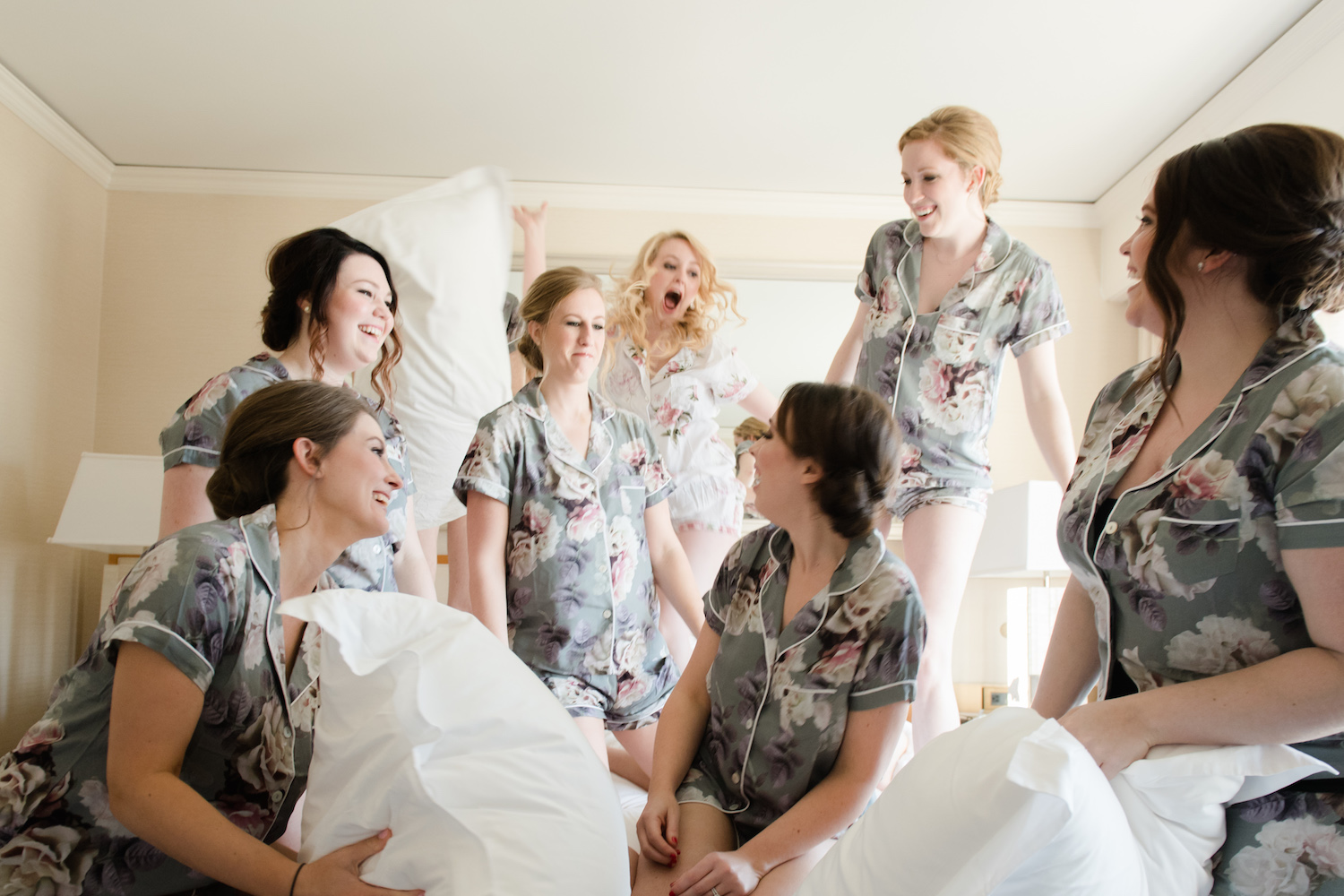 The brides and her bridesmaids kicked off the day with a pillow fight in the bridal suite. We can't help but note how the colors throughout the entire day coordinated - from the floral satin pajama sets of the bridesmaids to the reception florals. Well done, Margie!