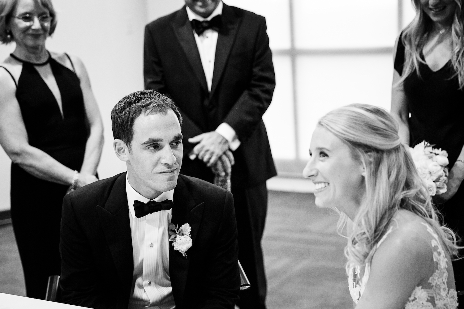 Groom looks over at bride during their ketubah signing at the Chicago History Museum.