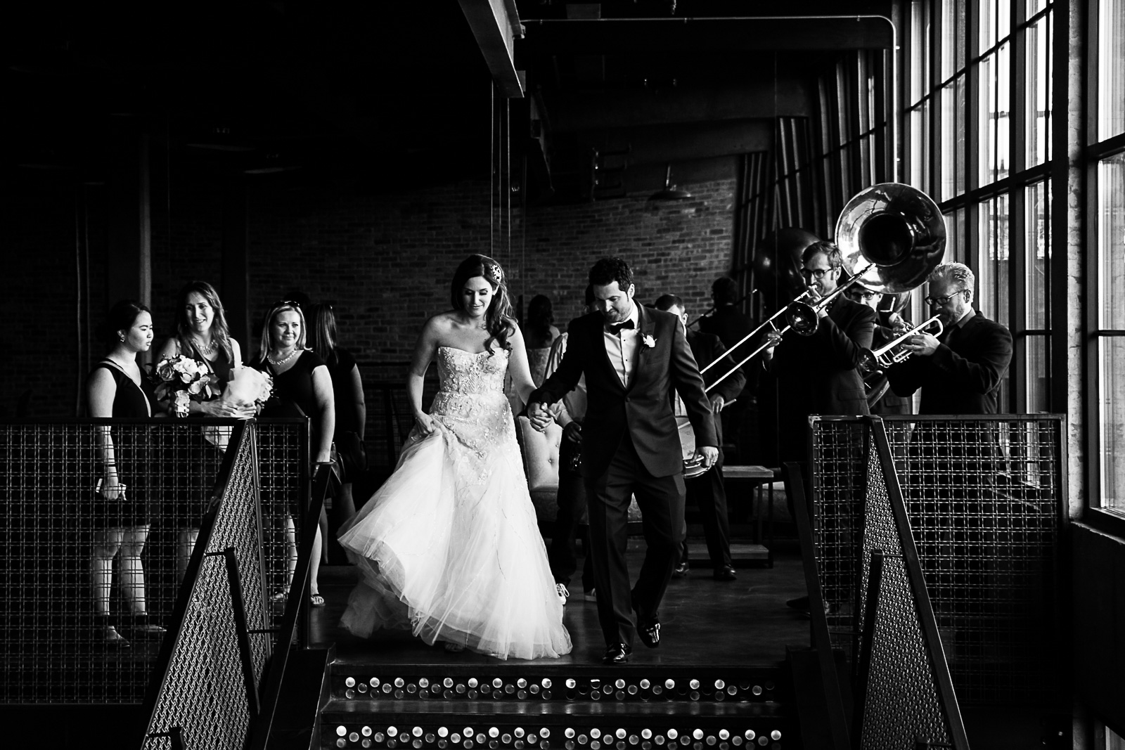 A band plays as the bride and groom festively enter cocktail hour at their wedding in Chicago's West Loop.