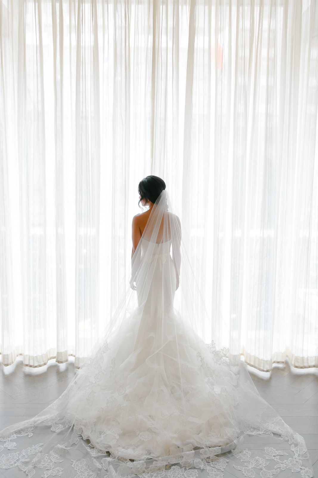 Bridal portrait in front of giant windows in The Peninsula Chicago.
