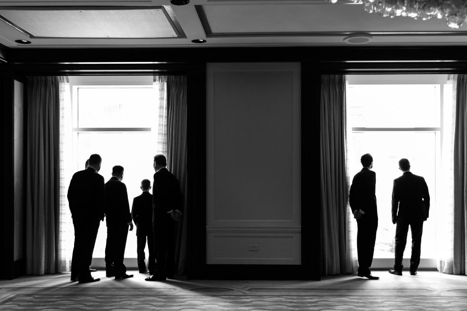Chicago documentary wedding photography - groom and friends look out window's of the Peninsula down to Michigan Ave.