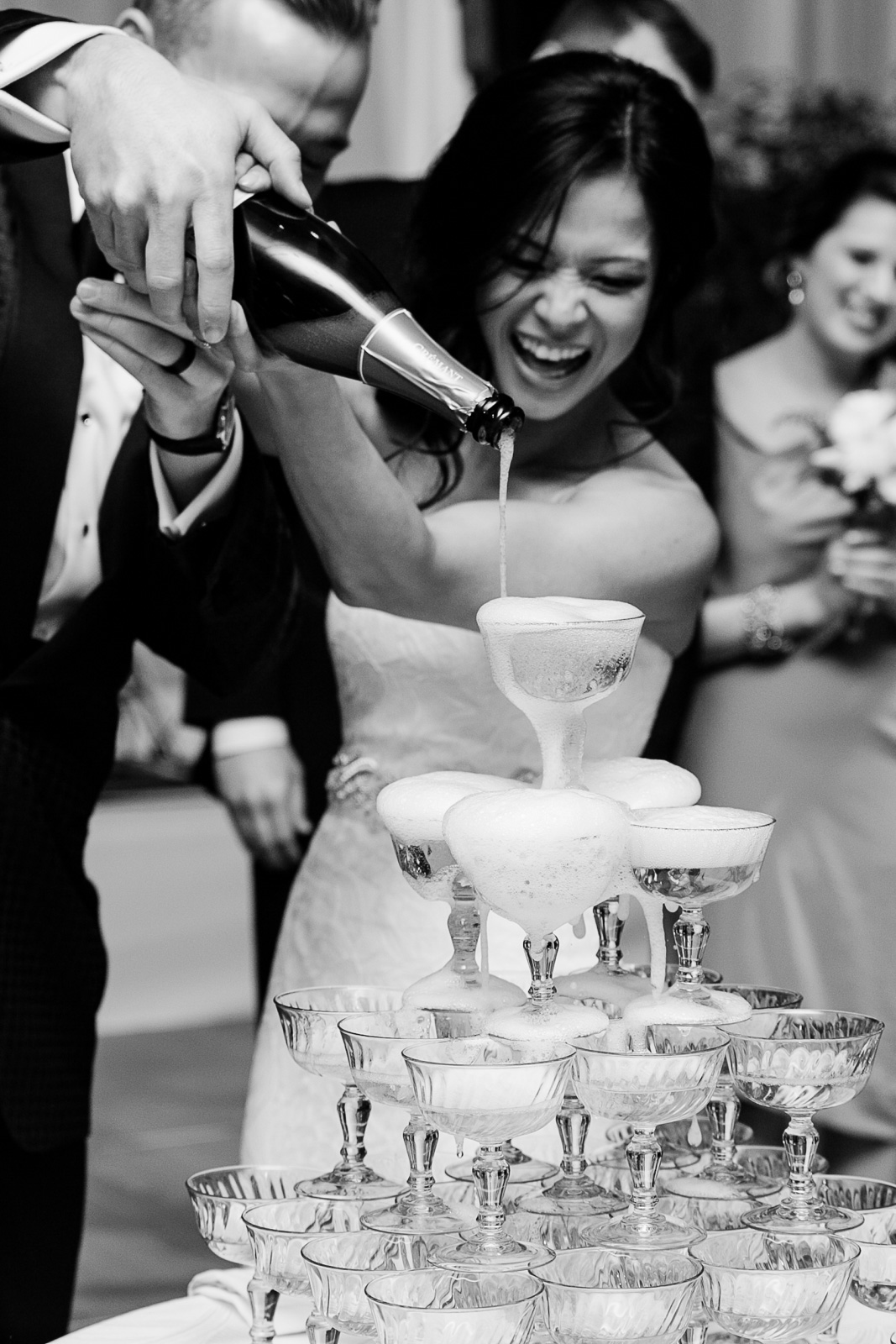 A bride and groom pour a champagne tower in the grand ballroom at Chicago's Peninsula Hotel.