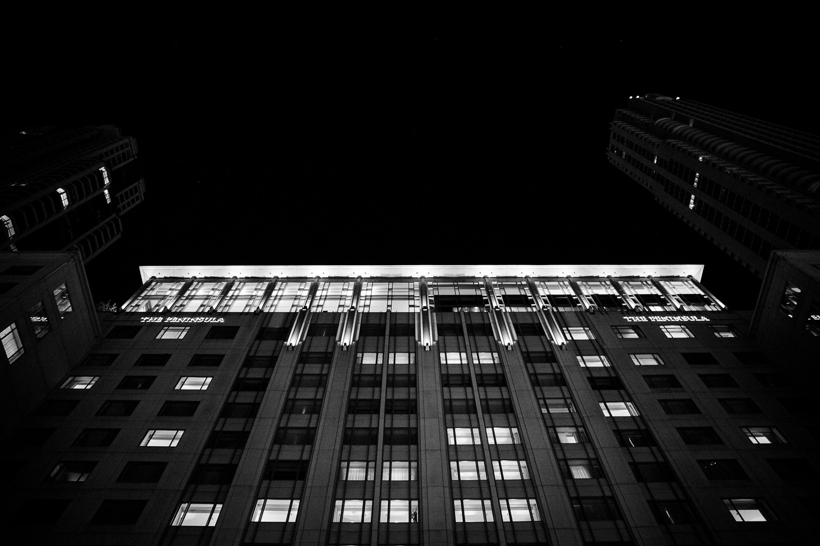 A black and white exterior shot of the facade of the Peninsula Hotel looking up toward the lights of the grand ballroom during a fabulous wedding reception.