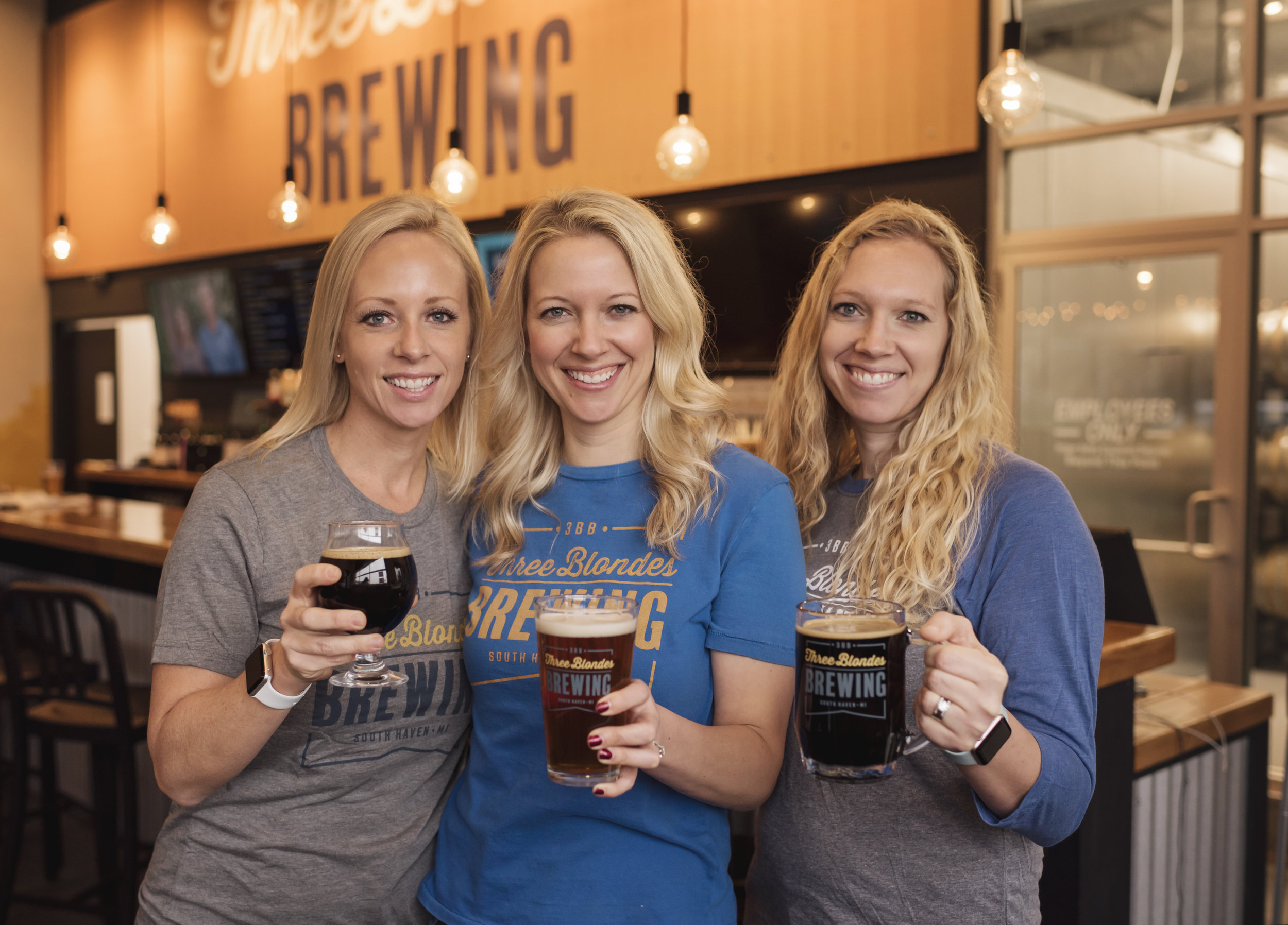 3 blondes holding beer in front of bar.jpg
