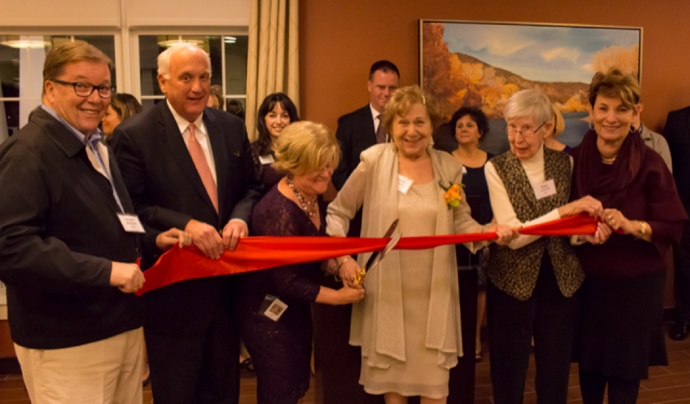 The Branches Executive Director  Kelly Arnao  shares the scissors while State Senator Richard Ross, far left, and State Representative Betty Poirier, far right, hold the ribbon with Benchmark CEO  Tom Grape  and the first two residents of The Branches, Elma Underhill and Harriet Weintraub.