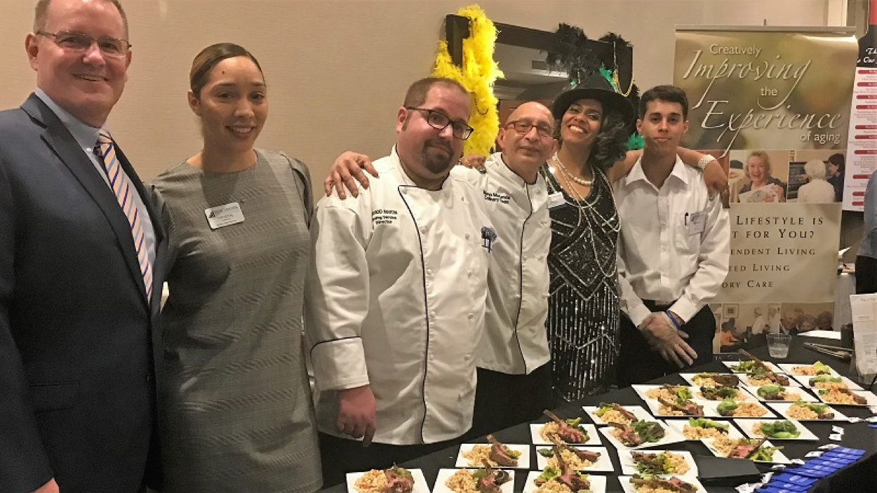 From left, Executive Director  Stephen Johnson , Harbor Care Director  Crystal Anderson , Dining Services Director  Jarrod Martin , Chef  Mario McKenzie , Server  Aisha Beauchemin , and Server  Moises Torres  staff the Leominster Crossing table at the DoubleTree by Hilton Hotel in Leominster, Mass.
