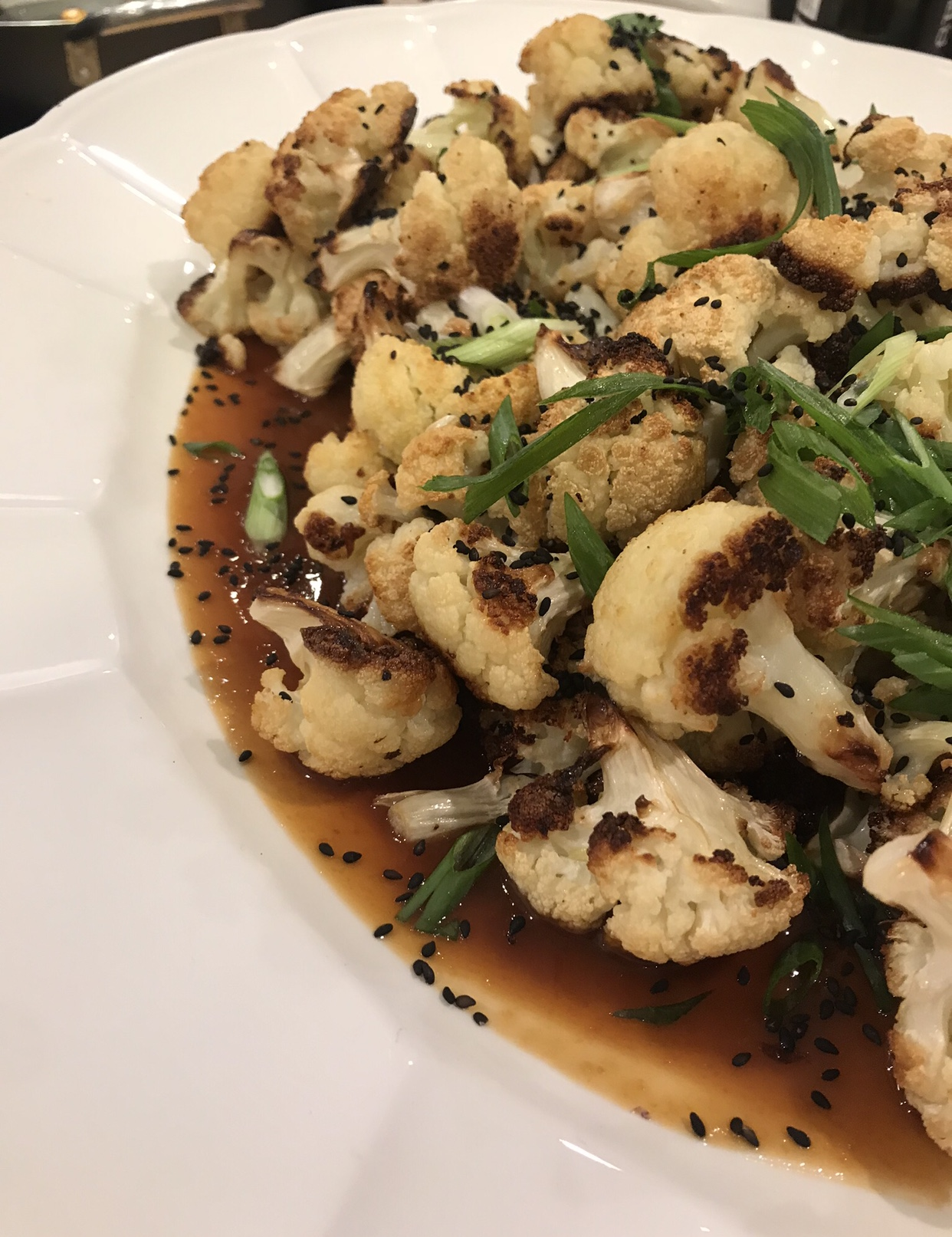 Serving Size: 12 people     Preparation time: 30 minutes        Ingredients:    5 Cauliflower florets, cut into 2 inch florets  1/3  cup sesame oil  4 Tbsp Grape seed oil   1/2 tsp salt  1/2 cup red or white miso   1/3 cup sugar   1/2 cup mirin   3 tbsp soy sauce   3 garlic cloves, microplane      Directions: Heat the oven to 500 degrees F. Toss the cauliflower in the sesame oil, grape seed oil,  and season with a little salt. Place on a baking tray lined with baking paper and roast for 25 minutes, or until the cauliflower is browned.      Meanwhile, In a sauté pan, on medium low heat, pour mirin, allow it too cook down for 30 seconds, it should start bubbling. Then add miso paste, stir in for 3 minutes. Then add sugar, soy sauce, and garlic. Cook on low for 2 minutes,  pour over the roasted cauliflower, tossing it on the tray to coat well. Continue to roast for a further 5 minutes, or until the miso sauce starts to caramelize.      Remove cauliflower  from the oven, transfer to a serving plate, scatter with spring onion and toasted sesame seeds, and serve. Enjoy