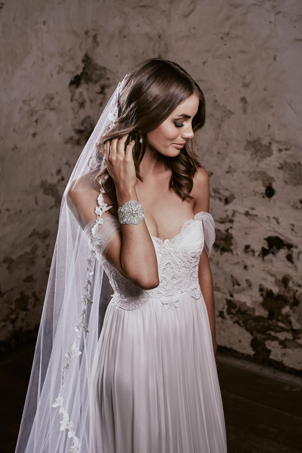 Brooklyn - Inspired by a sense of bohemian free-spiritedness and the sexiness that comes with effortless elegance, the strapless sweetheart neckline – finished with delicate ivory fringing – is both youthful and timeless. A low, exposed back, finished with the romantic Anna Campbell silk bow, injects a sense of playfulness and modernity into an otherwise classic bridal silhouette. An ivory guipure vintage lace detail at the end of the train adds an unexpected and unique finishing touch.Style with detachable, off-the-shoulder silk tulle sleeves for a different reception and ceremony look.