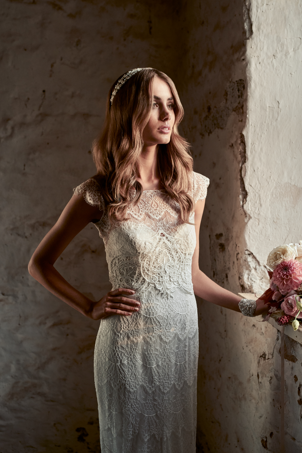Bella - Channeling understated romance and classic bridal elegance, the Bella is both youthful and timeless. A topper of fine ivory lace, finished with a high illusion neckline and delicate capped sleeves, is worn with the strapless Brooklyn sweetheart bodice dress. As the topper will come unattached to the strapless bodice, the Bella is the perfect dress to create different ceremony and reception looks – simply remove the topper after the ceremony for a strapless reception gown!