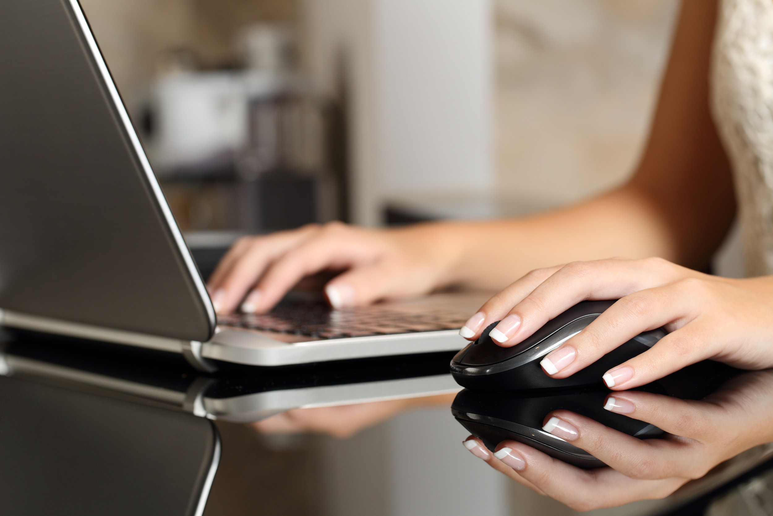 Business woman hands working with a laptop and a mouse.jpg