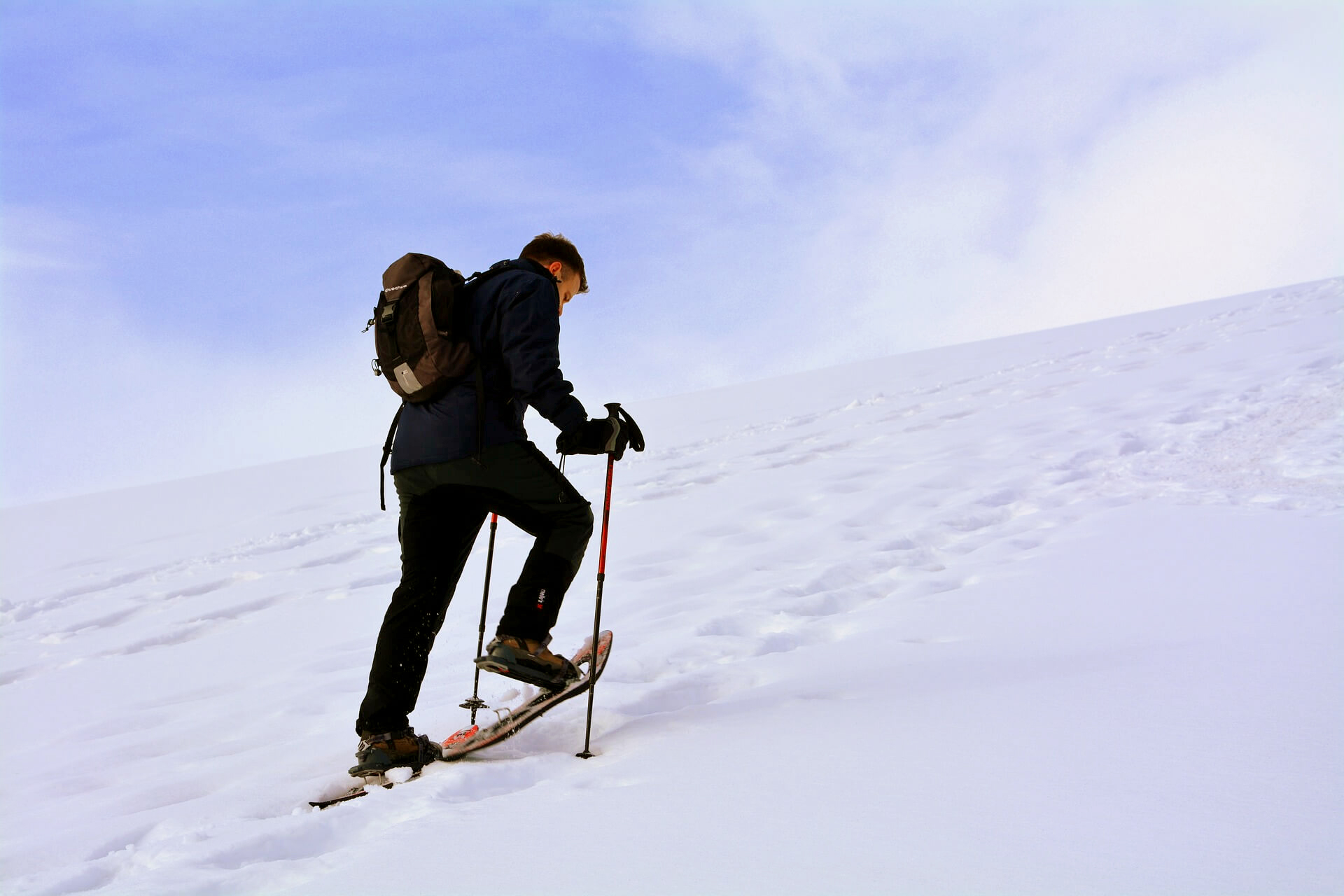 a hiker learning how to snowshoe uphill