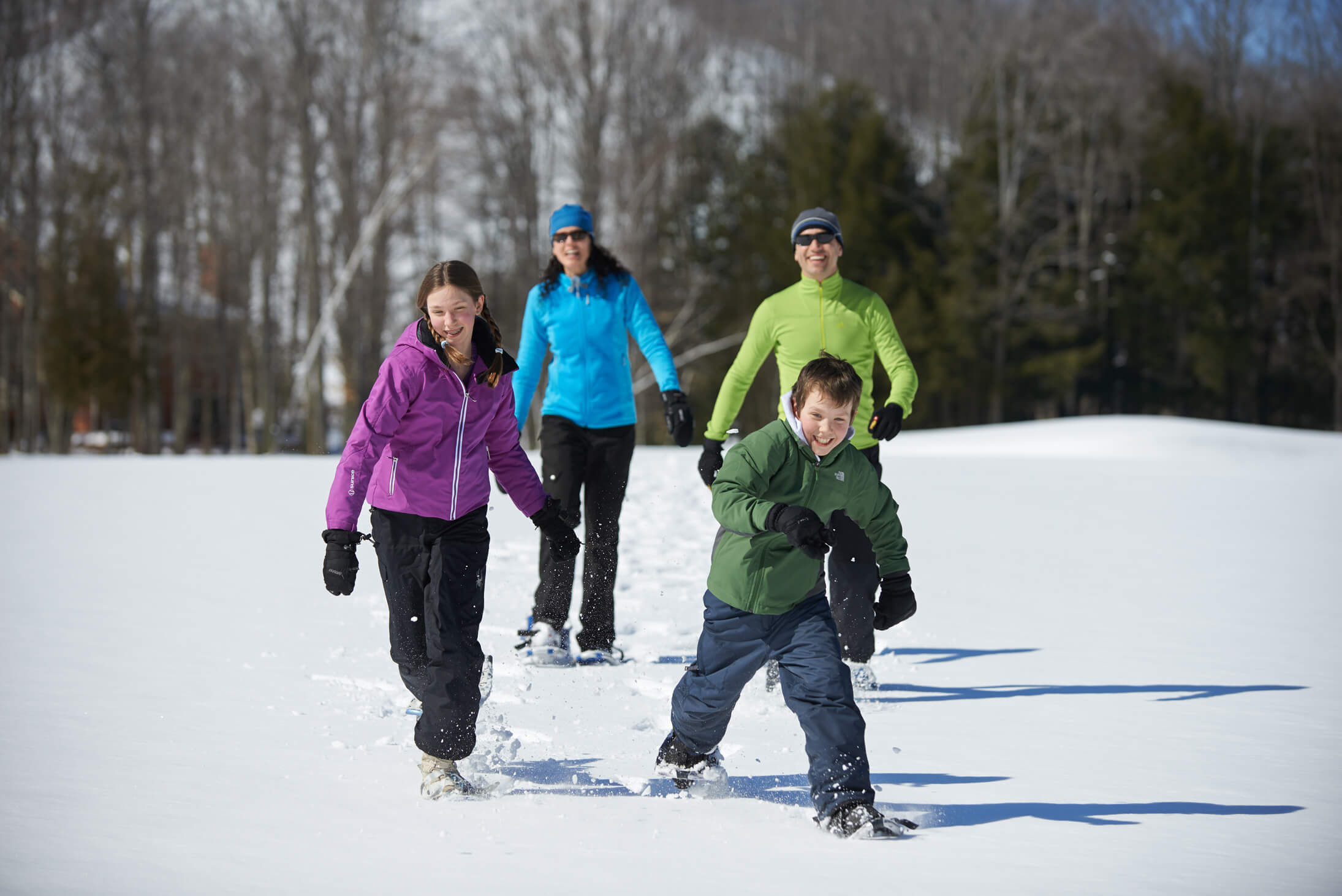 a family learning how to snowshoe