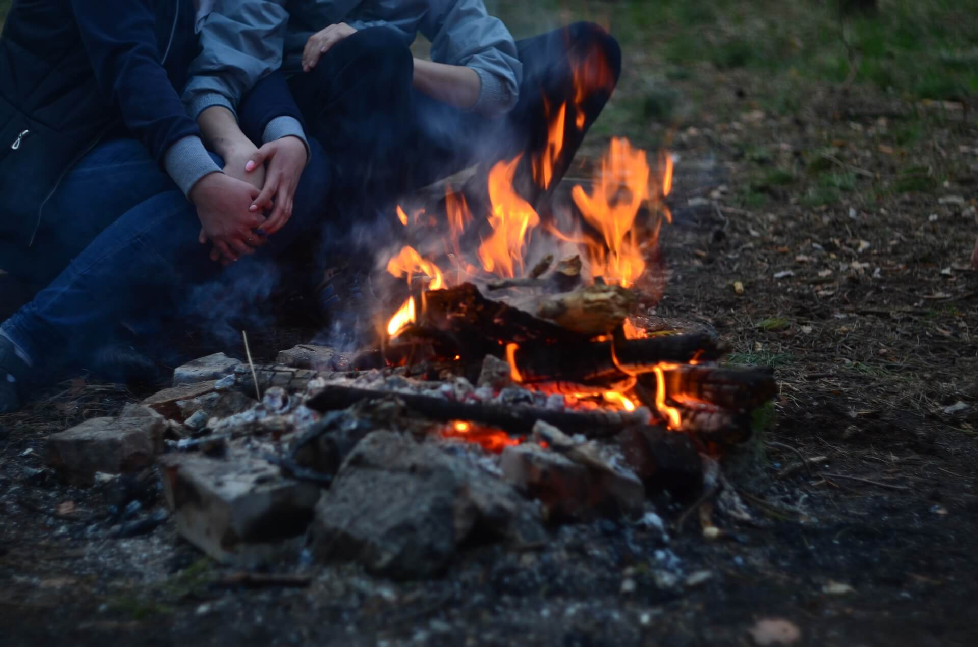 romantic campfire before couple having camping sex outside