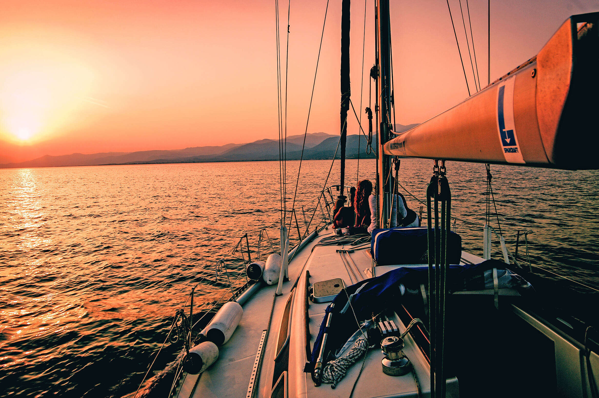 a couple enjoys the sunset on a romantic sailing outdoor date