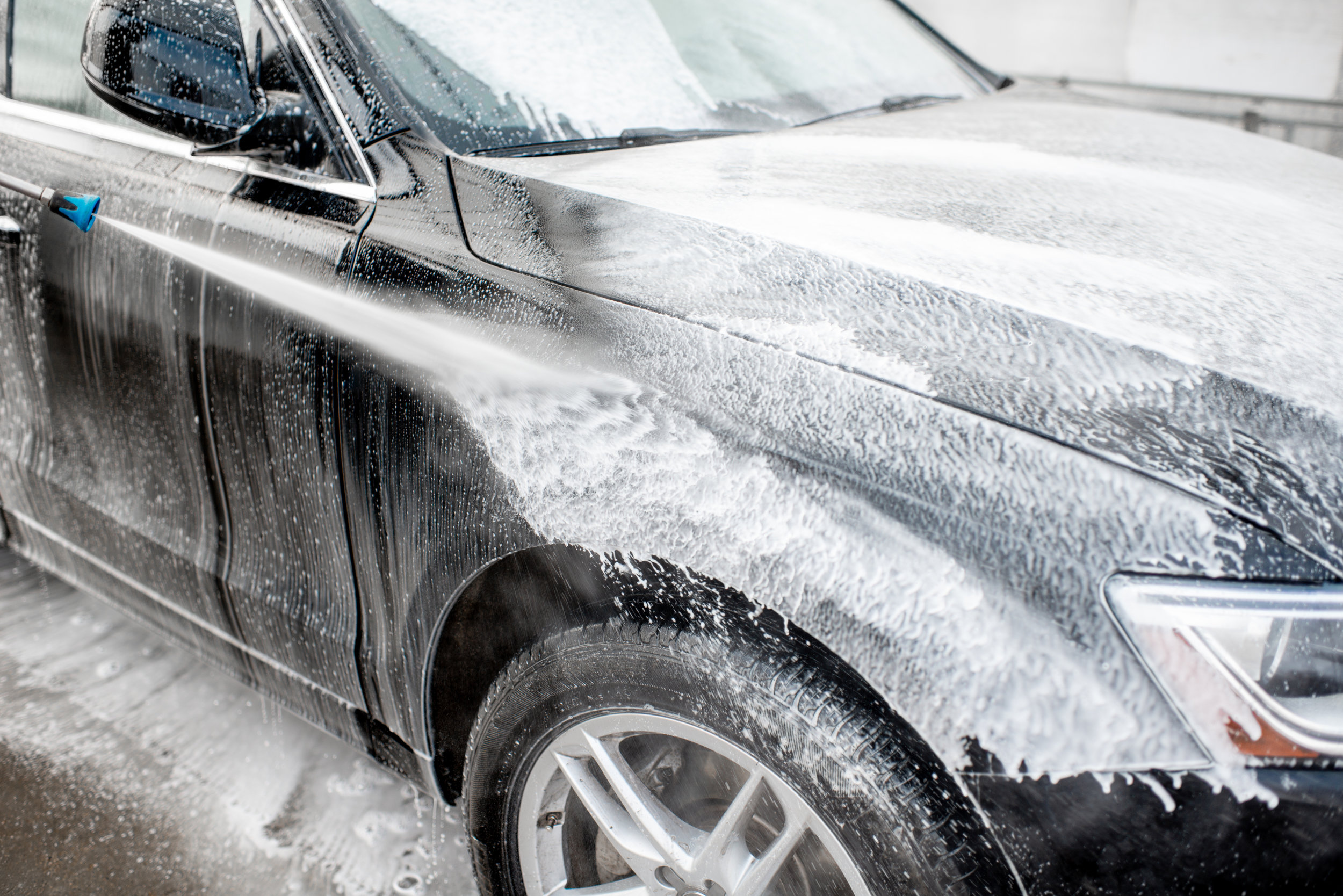 Close-up of a car under the water jet during the washing process on a self service car wash