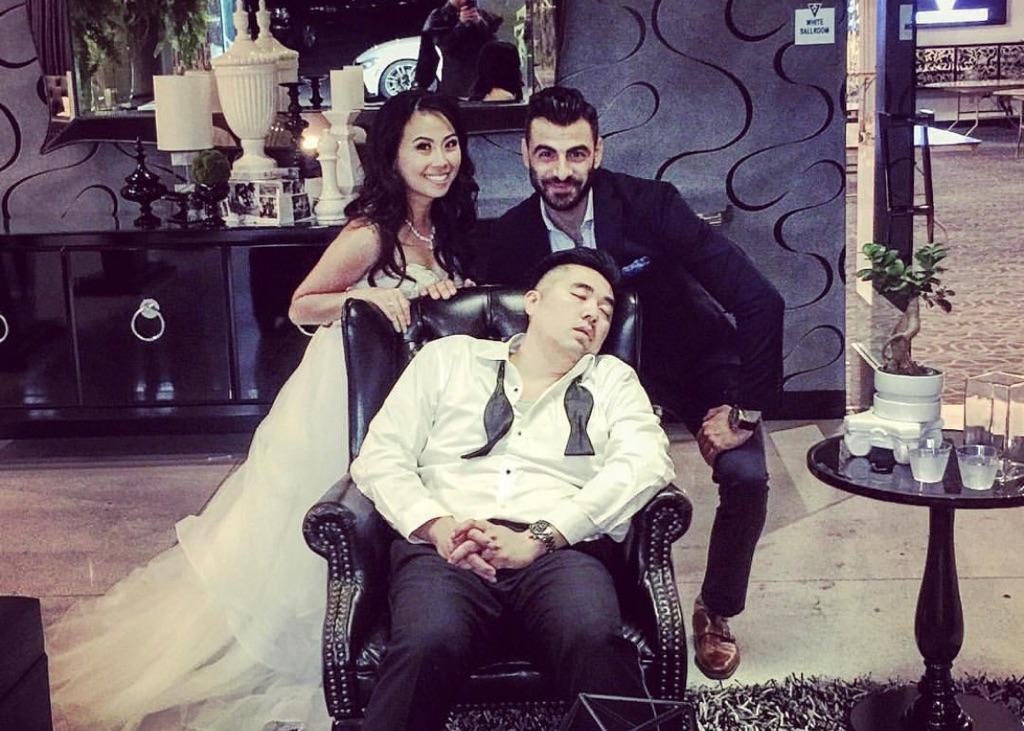 a young groom asleep inside of vertigo event venue after a wild wedding with his bride and vertigo's manager behind him smiling
