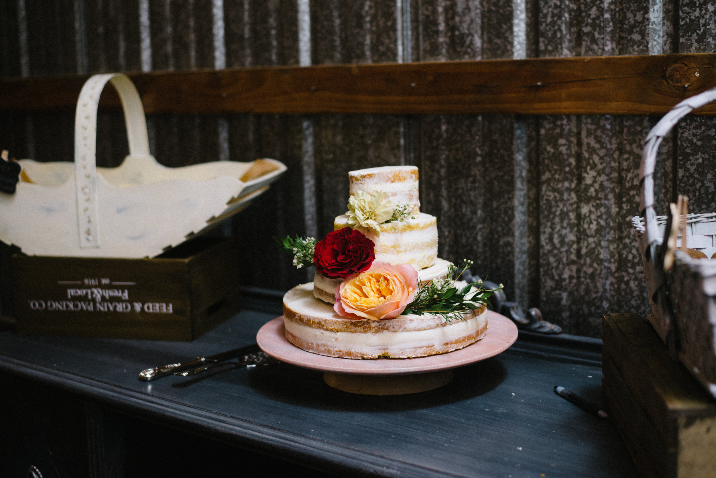 A naked cake adorned with simple and elegant garden roses