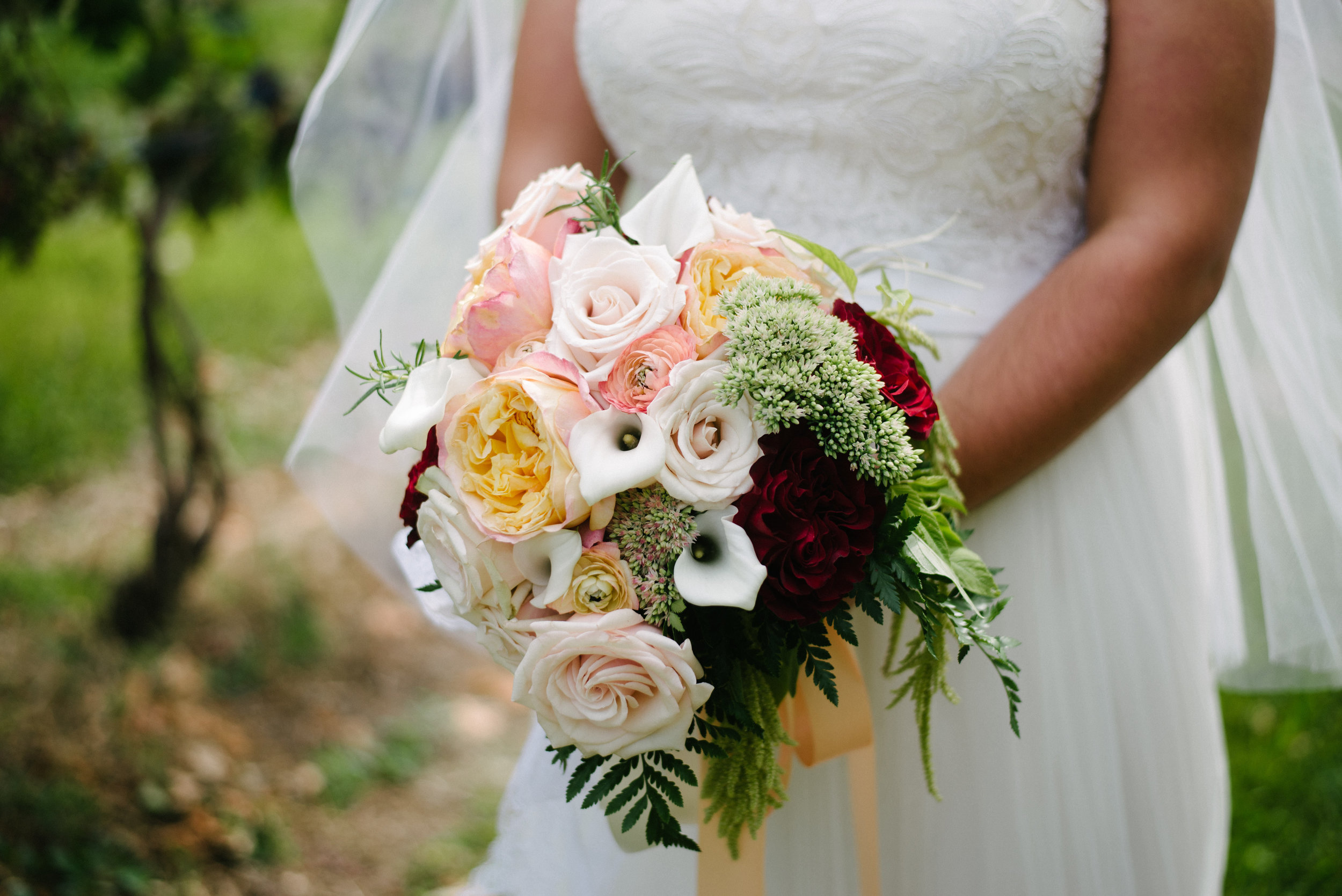 A hand-tied bouquet with luxury flowers: garden roses, mini calla lilies, ranunculus, sedum, amaranth, and greenery