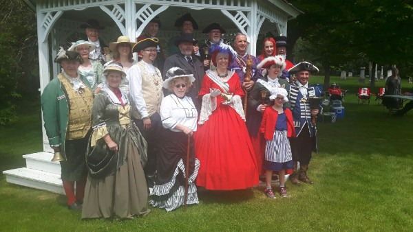 Group shot of participants with partners and supporters, showing Cobourg town crier Mandy Robinson front and center in her trademark red costume
