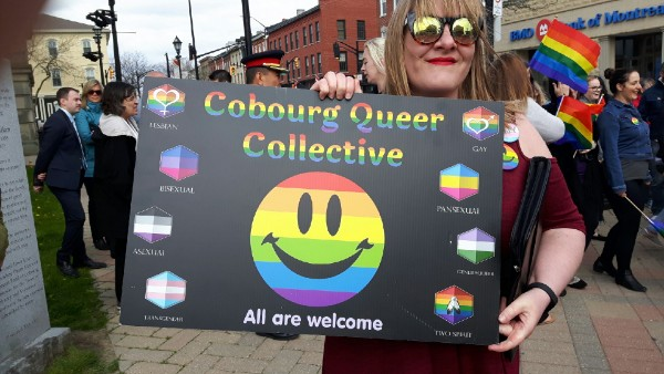 Organizer Ashley Bouman with a poster that shows variations on the Pride flag