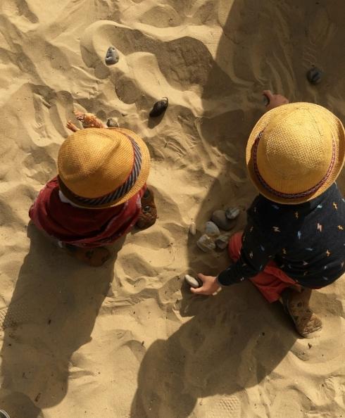 Boys on beach with rocks
