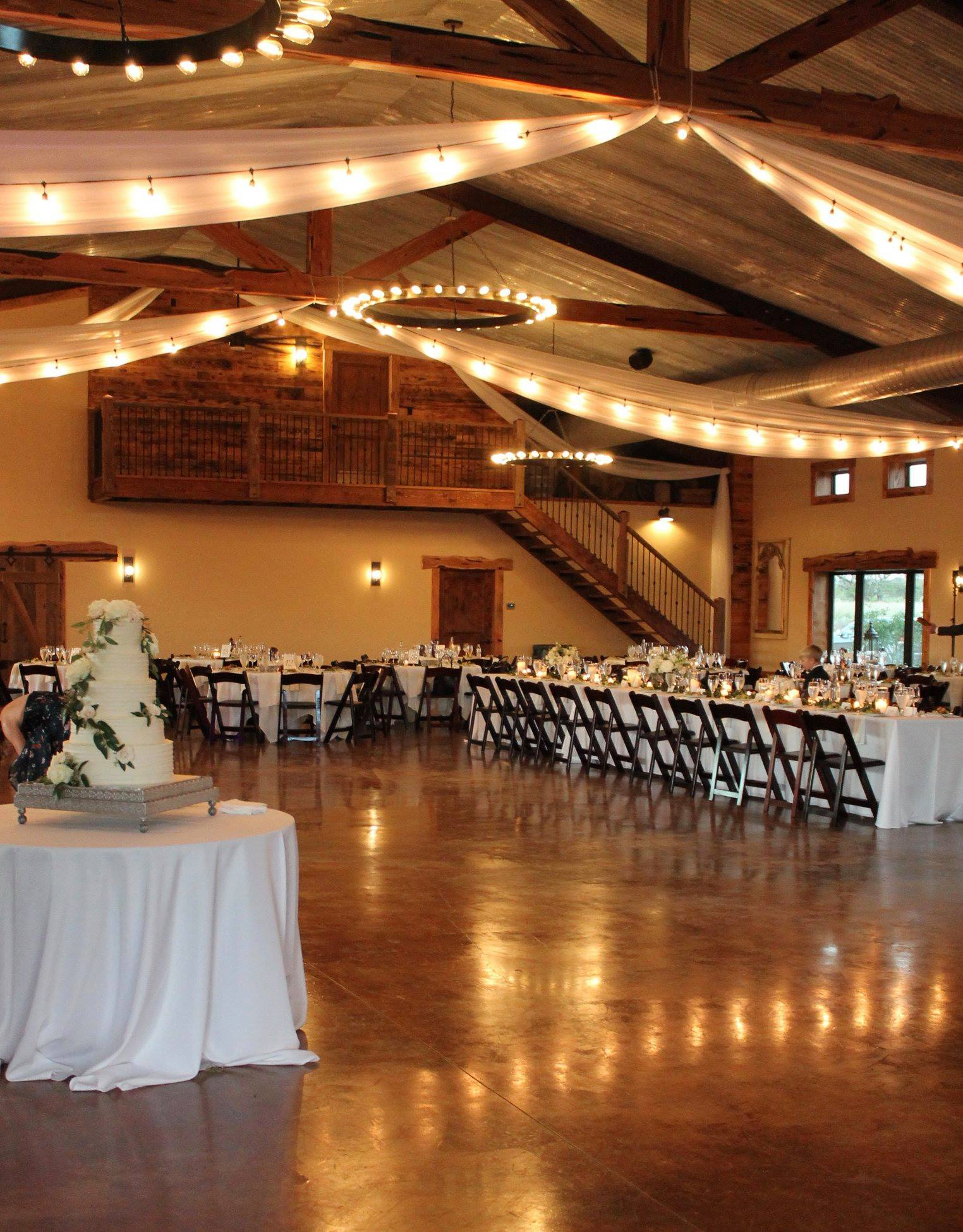 The Venue - The Venue at Rafter E Ranch is a rustic yet elegant lodge nestled on a private working ranch only minutes from Fredericksburg. The ranch harbors towering 100-year-old oak trees, miles of the blue-green waters of winding Bear Creek, as well as panoramic views of the rolling Texas Hill Country in the Pedernales Valley. The Venue offers beautiful indoor and outdoor ceremony sites to best accommodate all of your needs. If you are looking for a stunning view of the Texas Hill Country to wow your guests, we are the venue for you! Our spacious venue is 7,500 square feet and can easily accommodate 300 plus guests. Private suites for the wedding parties are available with the bridal suite upstairs overlooking the main room.