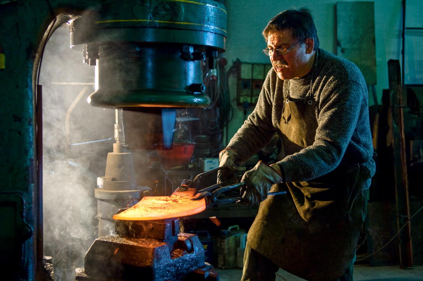 Le forgeron qui travaille au fer de proue de la gondole