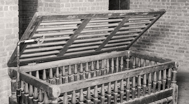 A confining bed that patients in a 19th-century asylum were caged in when they were unruly.