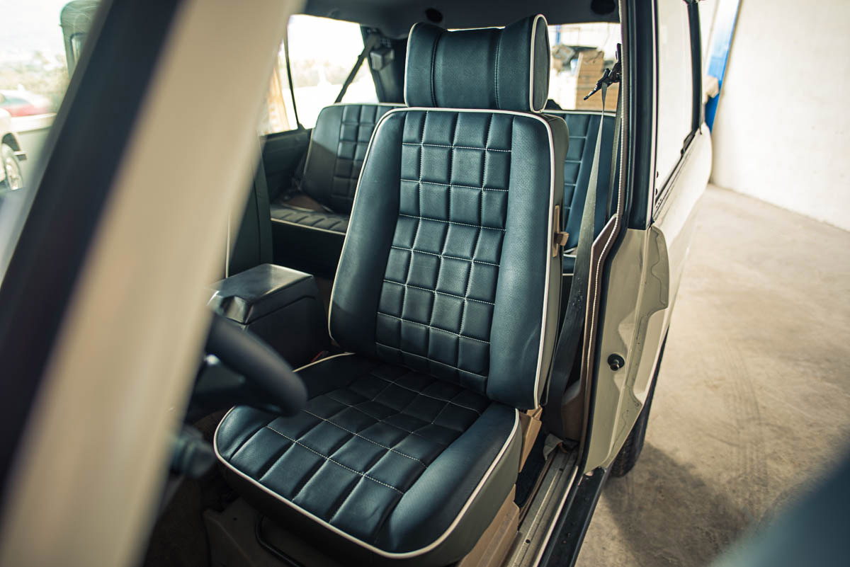 The interior of one of our custom 2-door Range Rover Classics, with seat faces in perforated black, seat backs and door panels in Moss Green, stitching and piping in white, and headliner in black. The interior was originally tan velour.