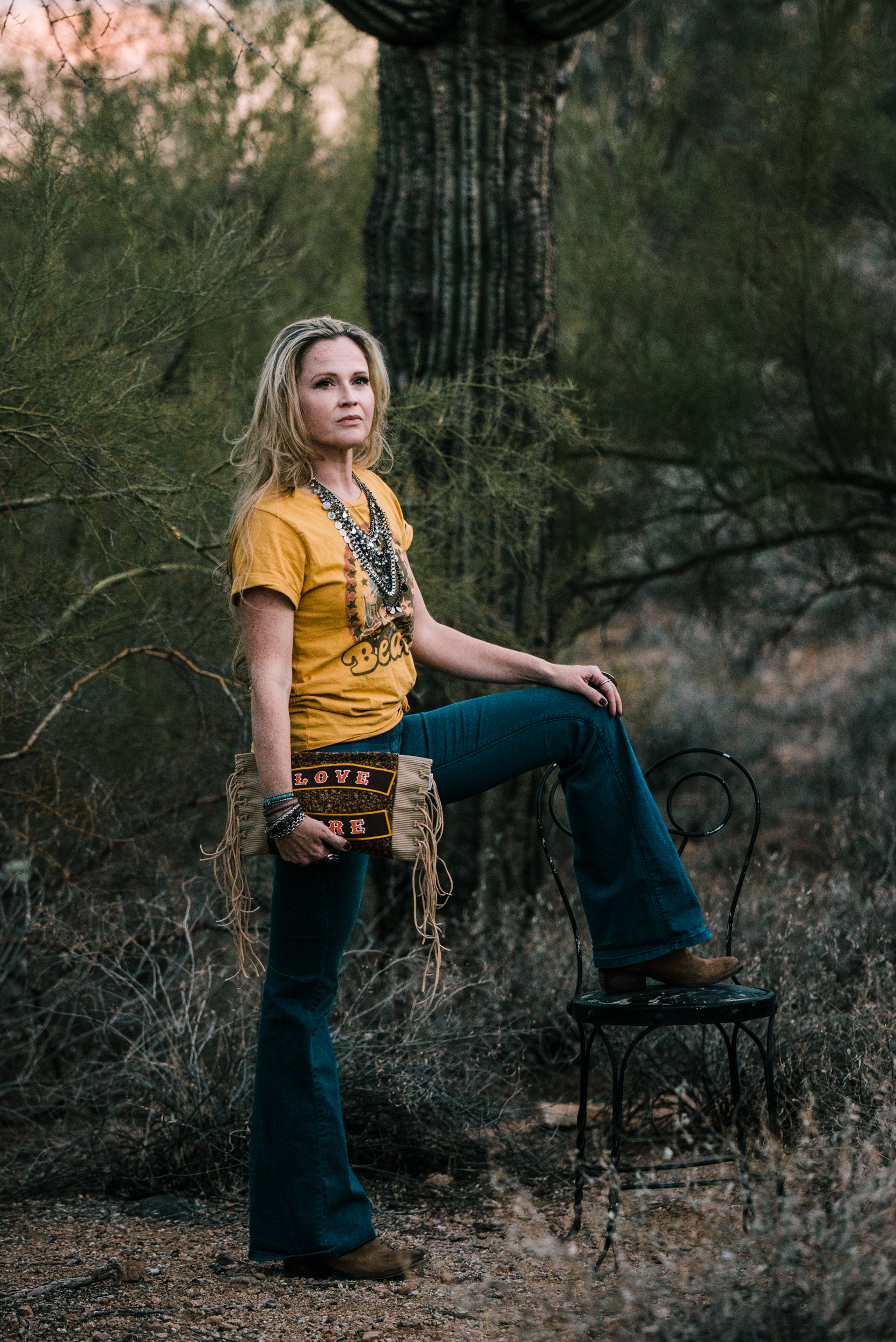 Beautiful Cortney owner of Hippie Momma Bags showing a gorgeous fringe bag in the Arizona desert