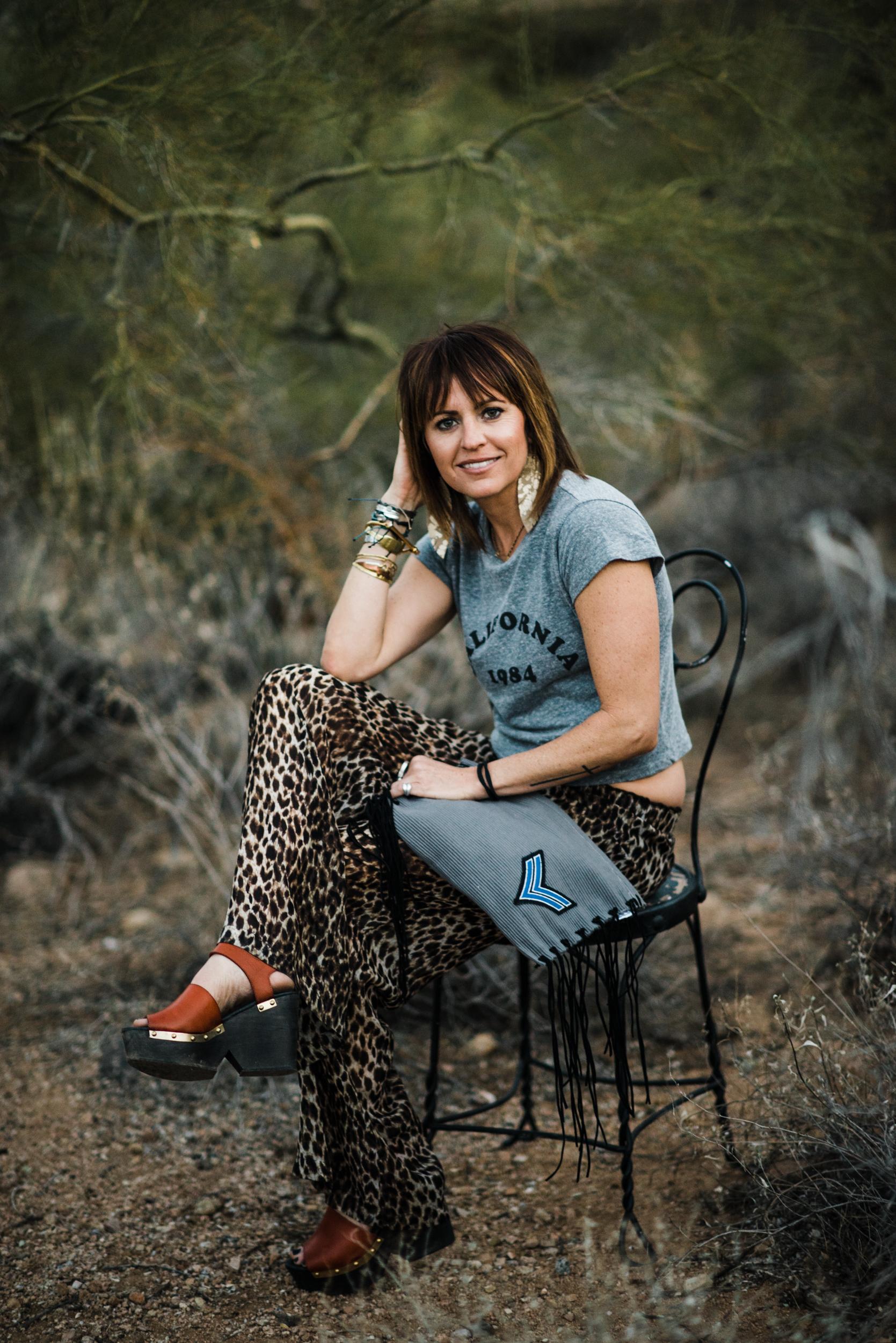 Lauren causally sitting in Arizona Desert with a gorgeous grey fringe bag