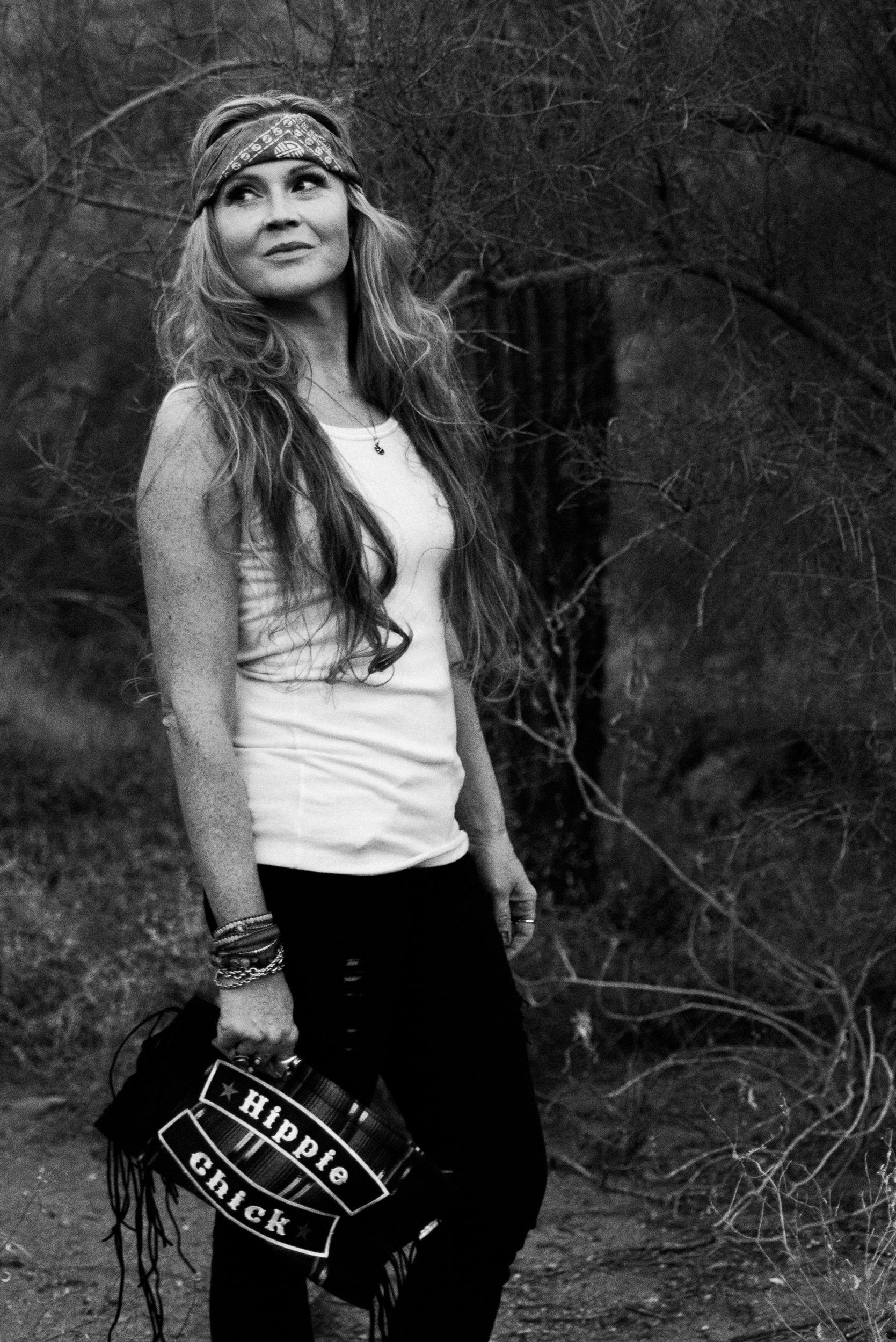 Beautiful Cortney owner of Hippie Momma Bags showing a black hippie chick bag in the Arizona desert a black and white photo