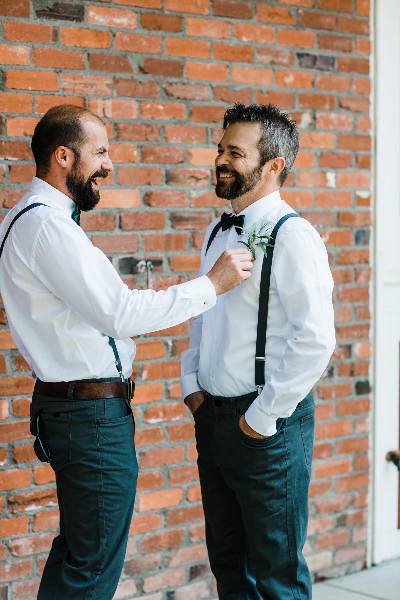 Colorado mountain wedding photographer at Brookeside Gardens grooms men goofing around
