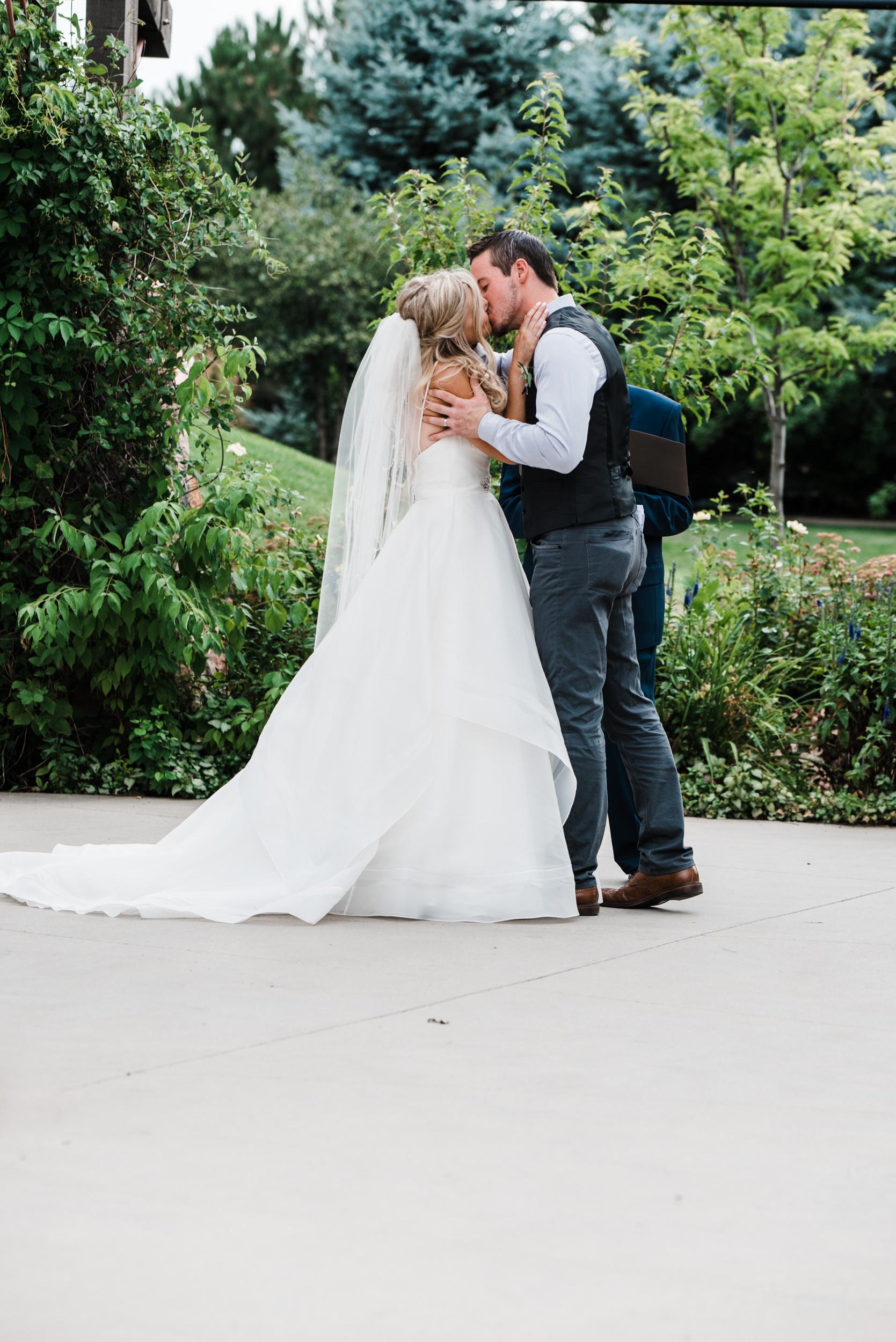 Colorado mountain wedding photographer at Brookeside Gardens wedding ceremony first kiss