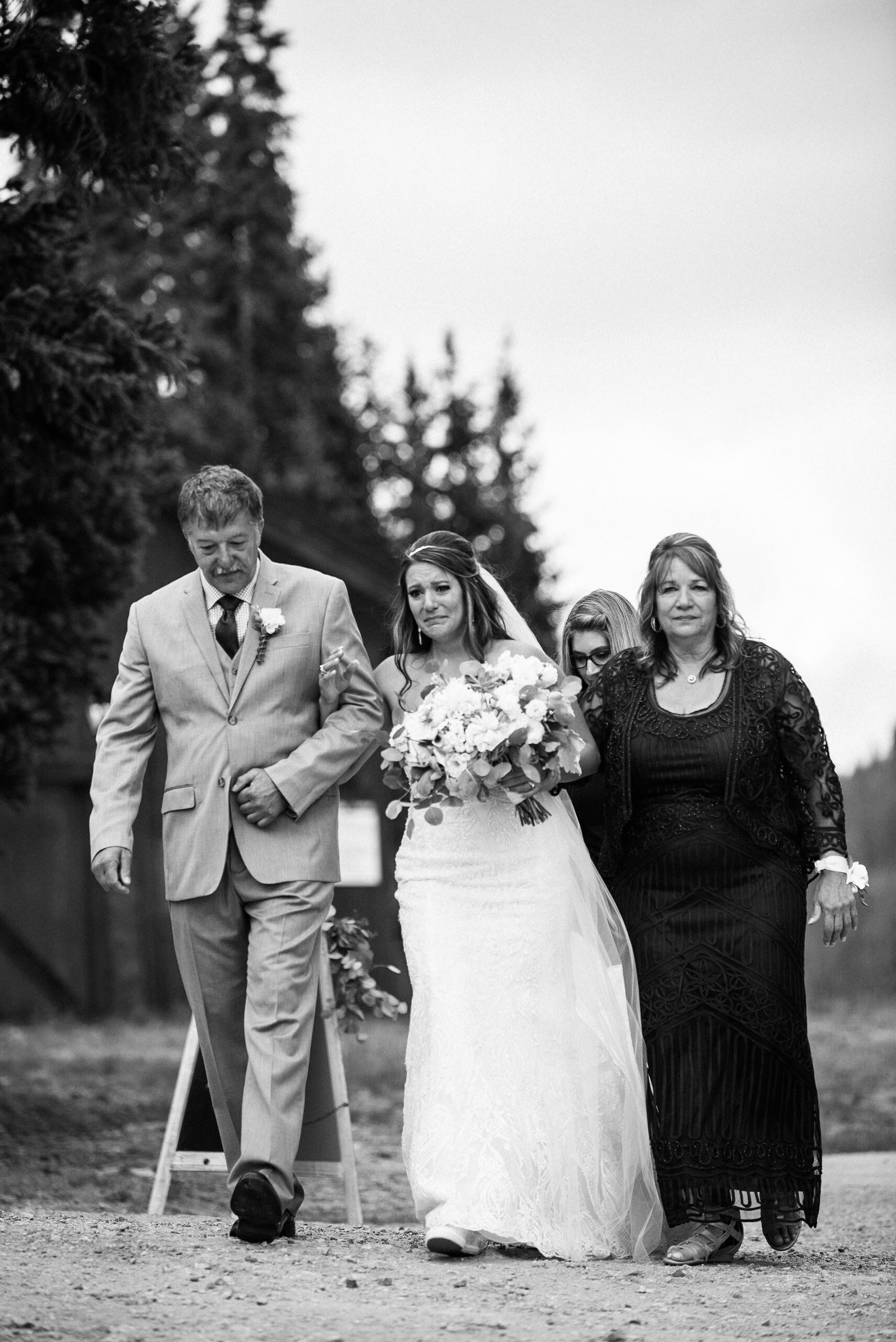 Bride and parents walking down aisle at Keystone, Colorado mountain wedding