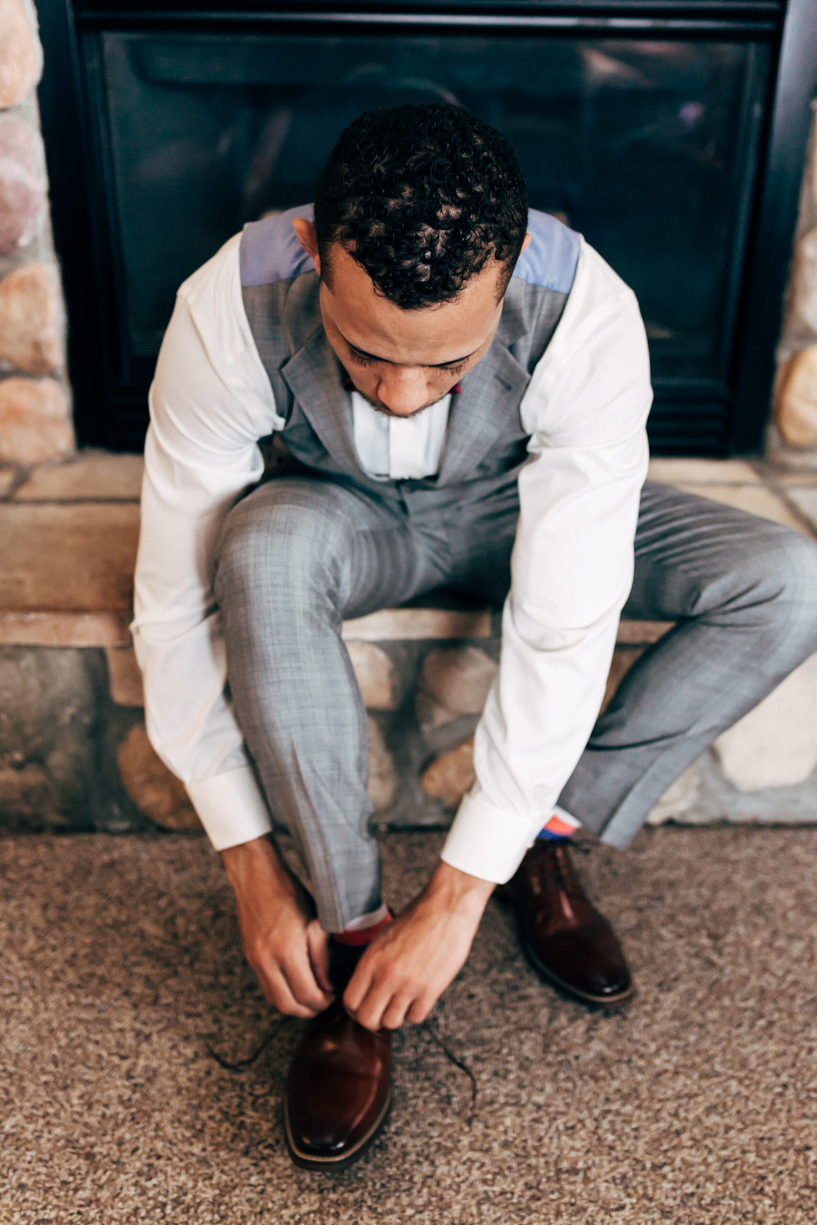 Groom putting on his shoes at the Lodge at Breckenridge wedding. Colorado wedding photographer.