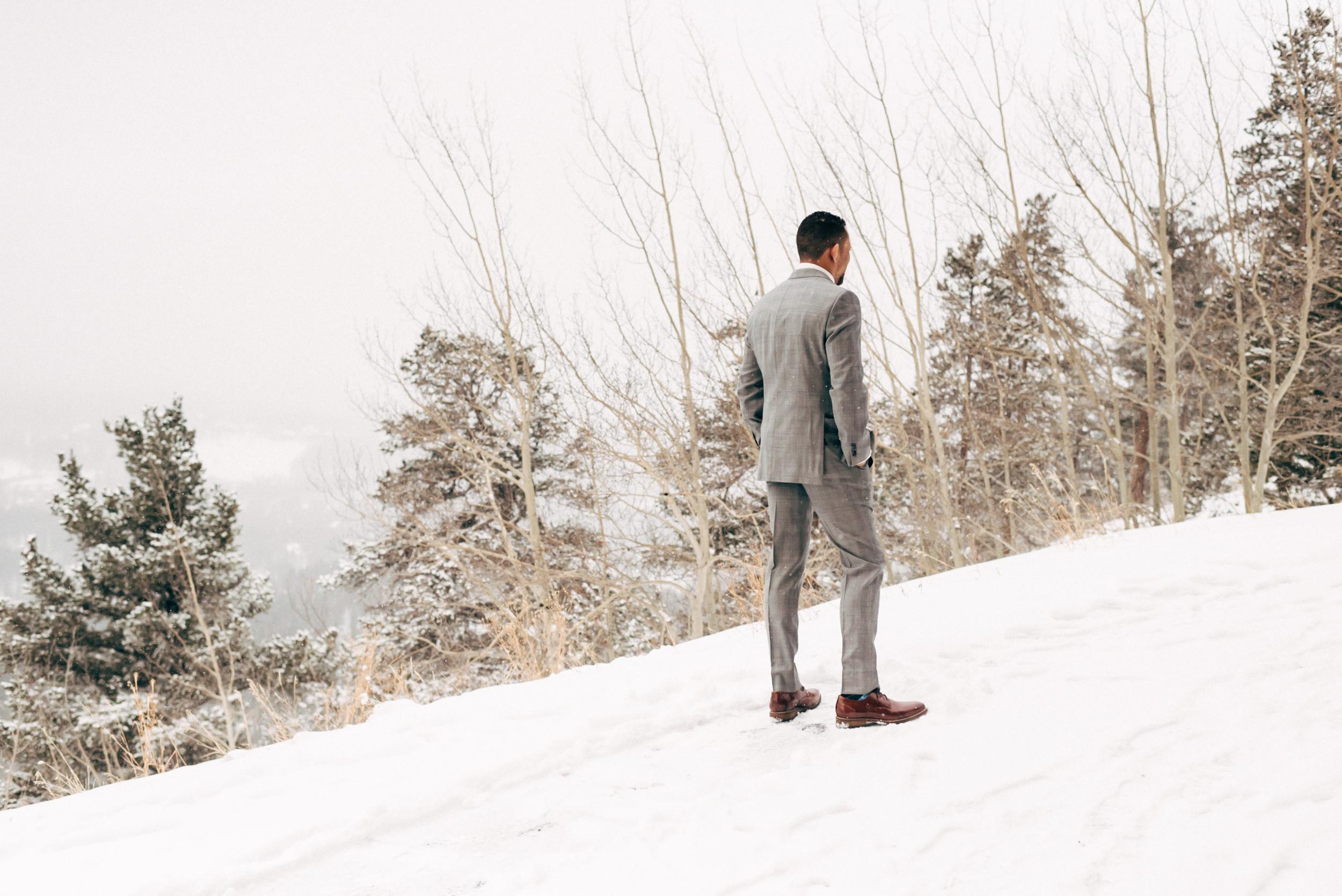 Groom waits for bride on mountainside in Breckenridge, Colorado, Colorado wedding photographer