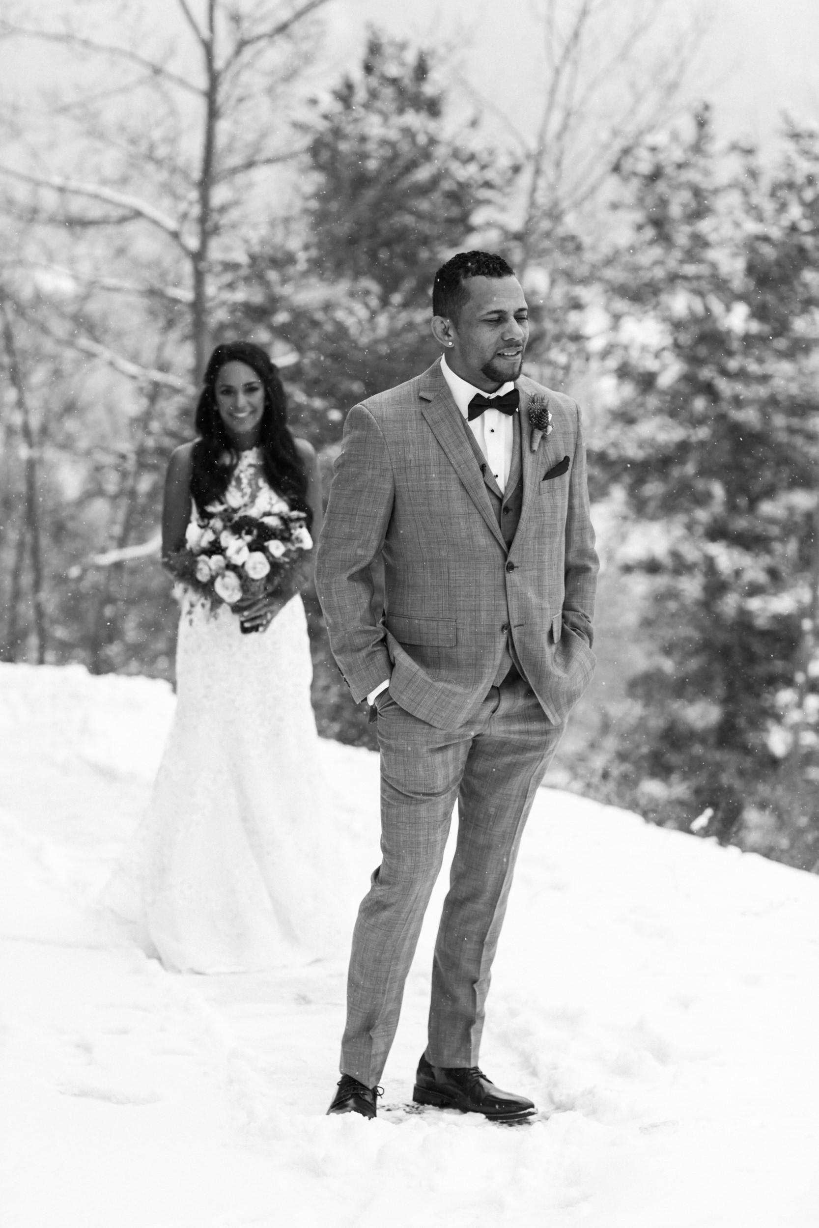 Bride behind groom on snowy mountain side in Brekenridge Colorado wedding.