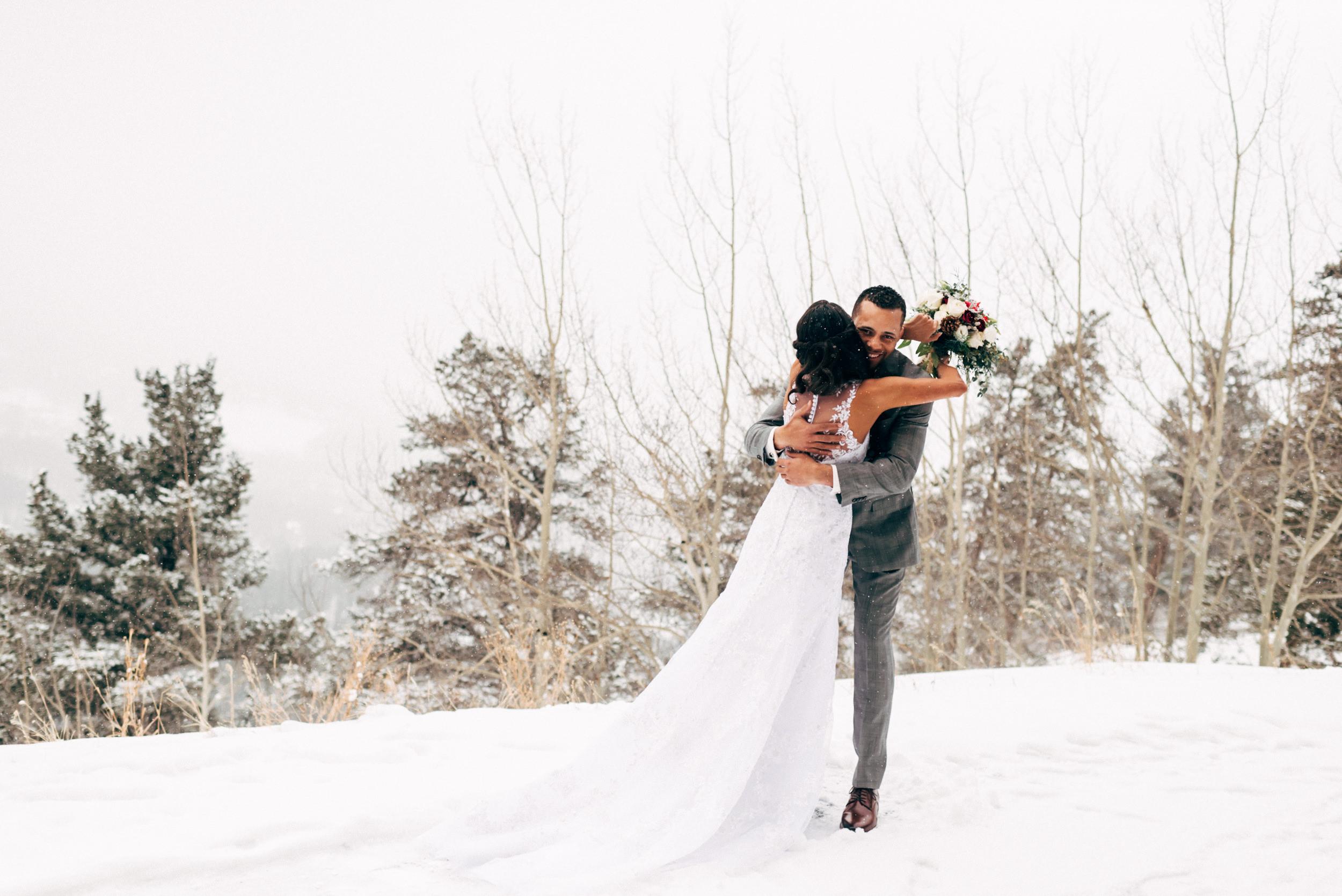 Bride and groom embracing on a winter wedding Colorado mountain side. Colorado Wedding Photographer.