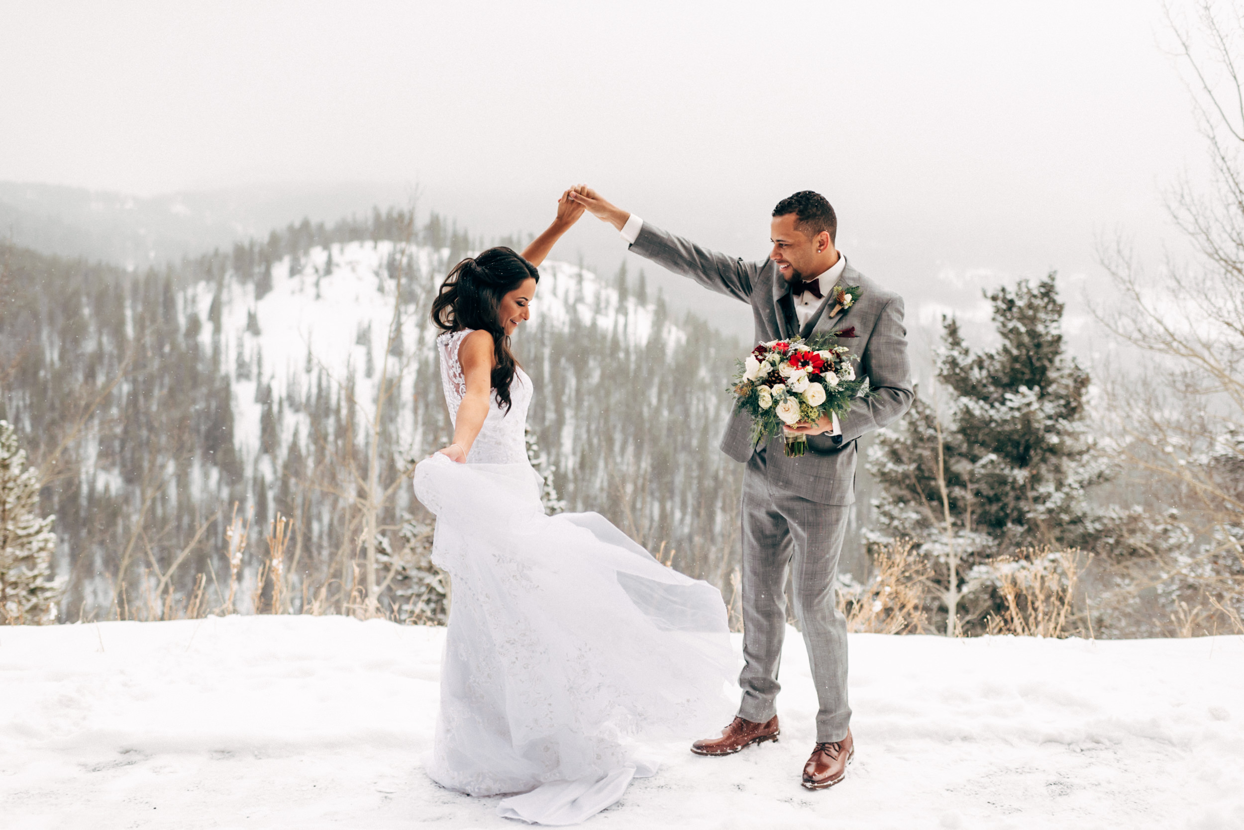 Bride and groom dancing on a snowy Colorado Breckenridge mountain top. Colorado wedding photographer.