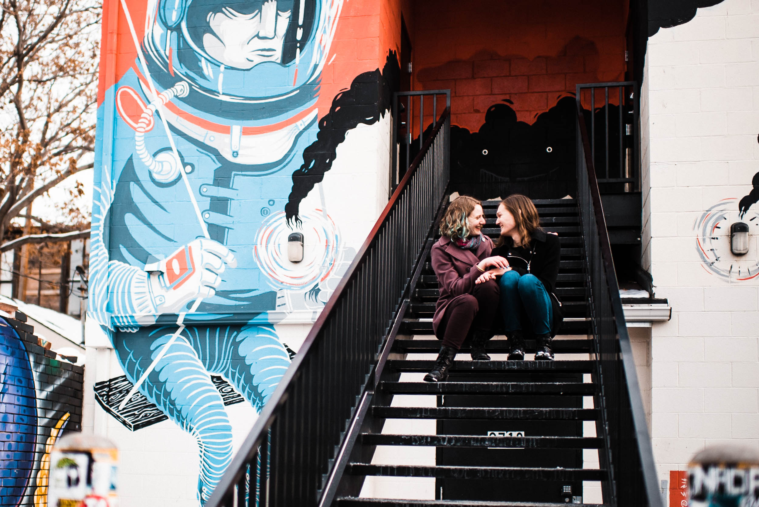 Same sex lesbian couple snuggling in a stairway in Denver Colorado RiNo art mural, RiNo Arts District, RiNo engagement session, LGBT wedding photographers, LGBT friendly wedding photographers, LGBT engagement photographers, Denver wedding photographers, Denver Engagement photographers