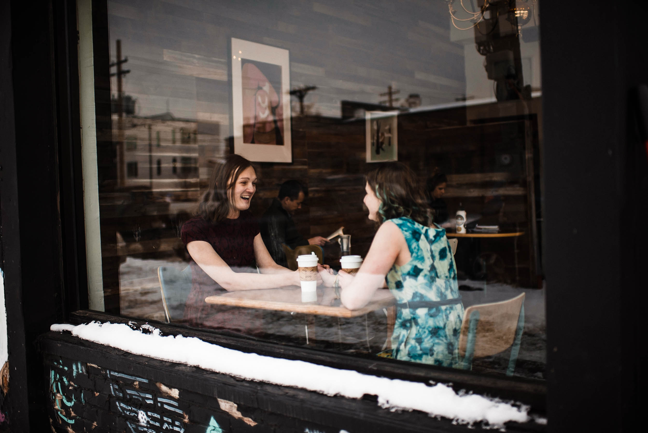 Sharing a cup of coffee at Creama Coffee in Denver Colorado RiNo art mural, RiNo Arts District, RiNo engagement session, LGBT wedding photographers, LGBT friendly wedding photographers, LGBT engagement photographers, Denver wedding photographers, Denver Engagement photographers