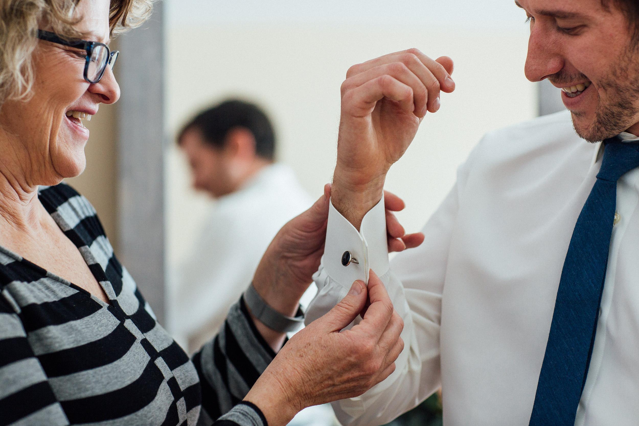 Mom helping groom get ready in Denver home wedding