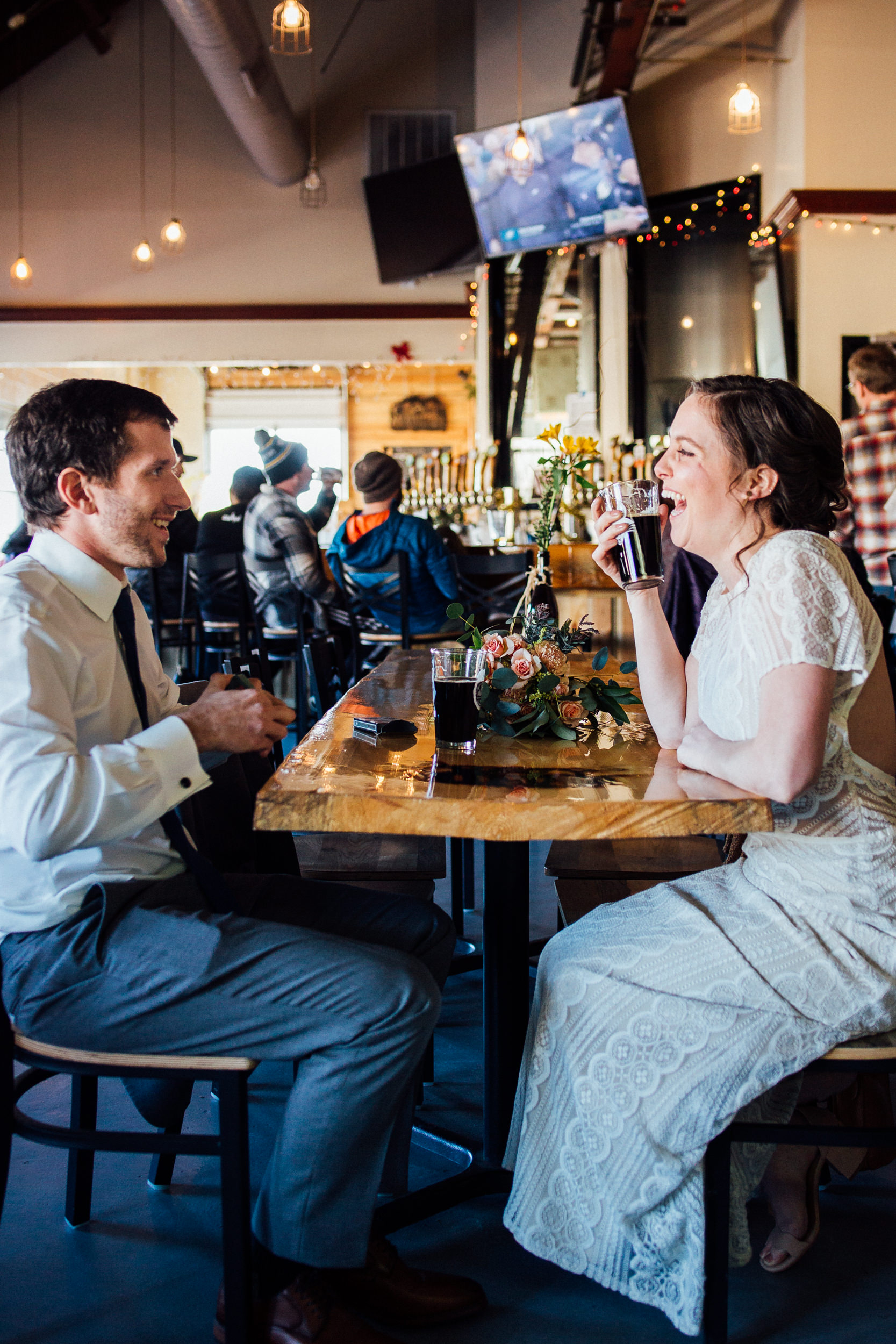 Laughs and beers in wedding dress-brewer wedding attire-Colorado wedding photographer