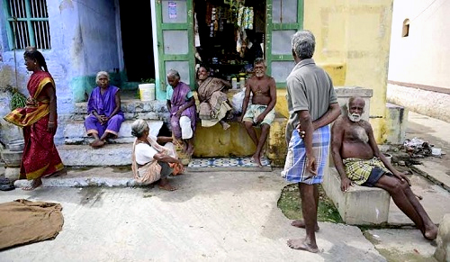 A group of elders gather outside a village corner shop. At times thalaikoothal is practiced even with their consent