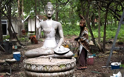 Sorceror by statue of buddha